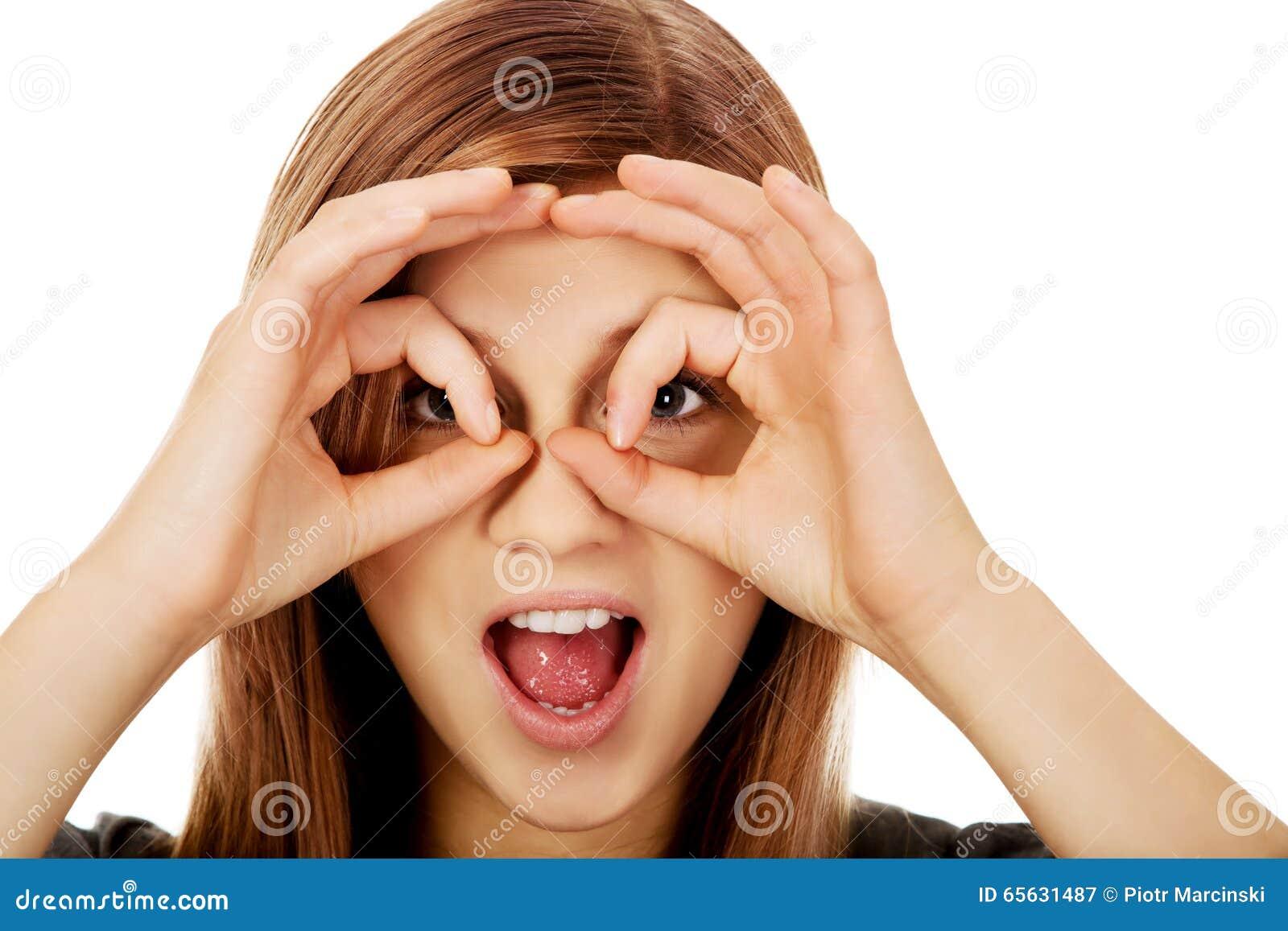 Femme adolescente faisant des mains de jumelles