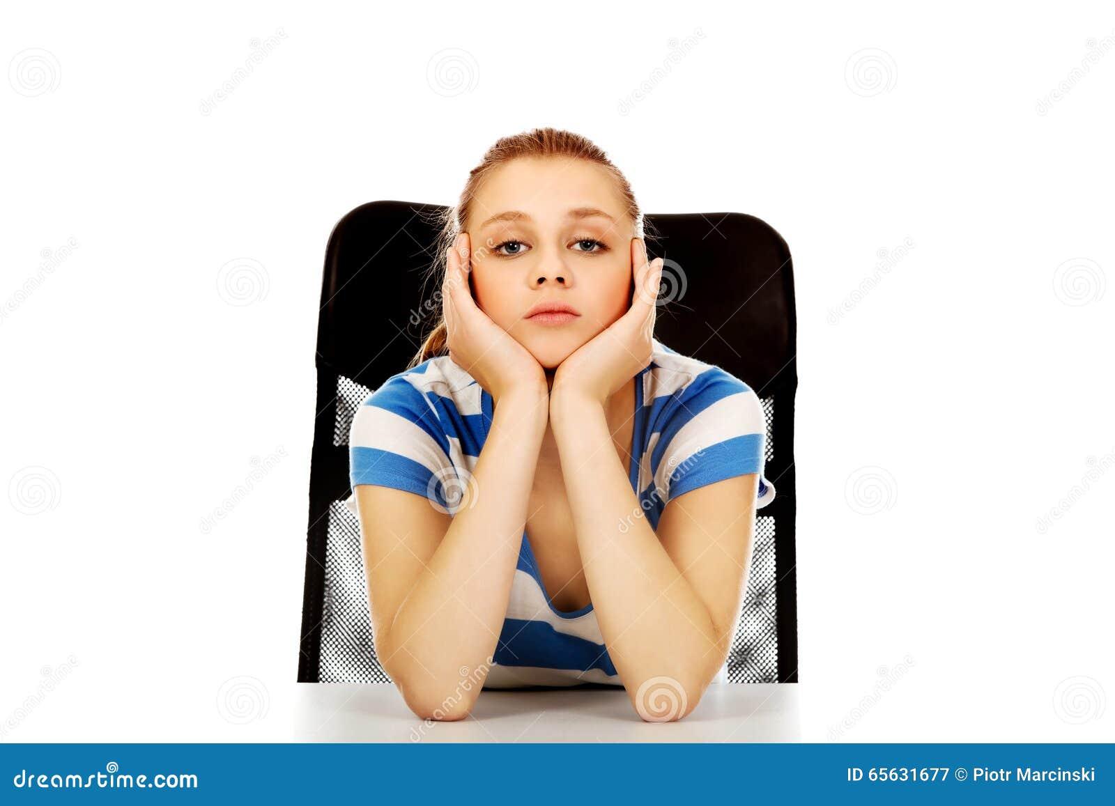 Femme adolescente fatiguée s asseyant derrière le bureau