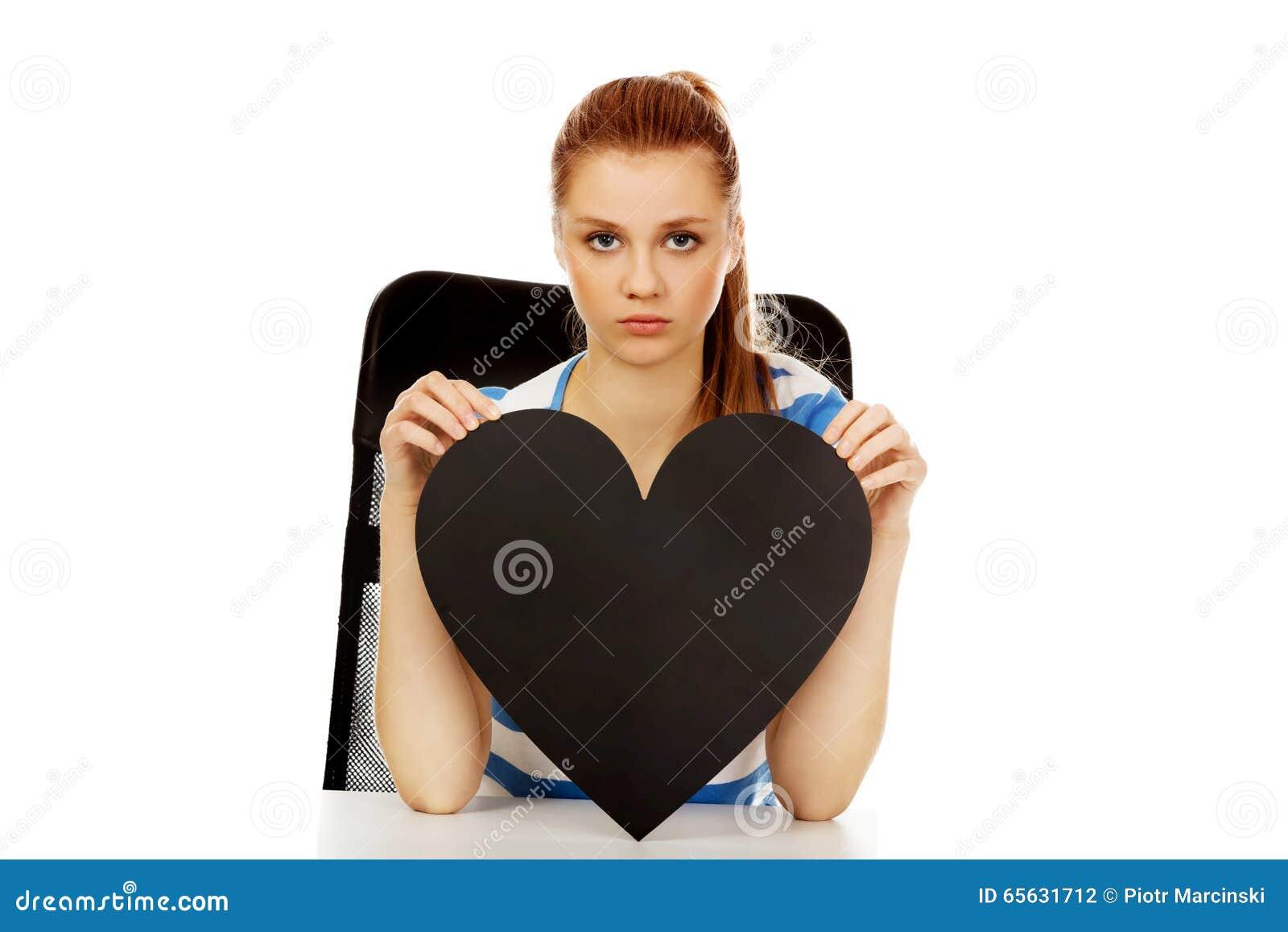 Femme adolescente inquiétée tenant le coeur de papier noir