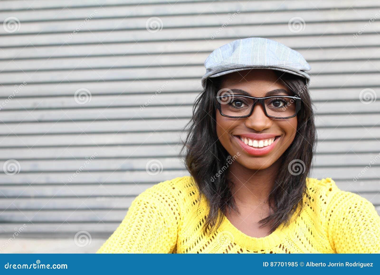 Femme africaine de hanche saine avec les verres et le chapeau de fantaisie montrant le bonheur avec l espace pour la copie