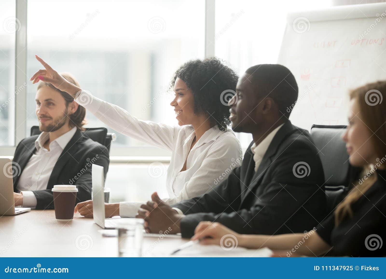 Femme africaine soulevant la main pour poser la question à la formation d équipe