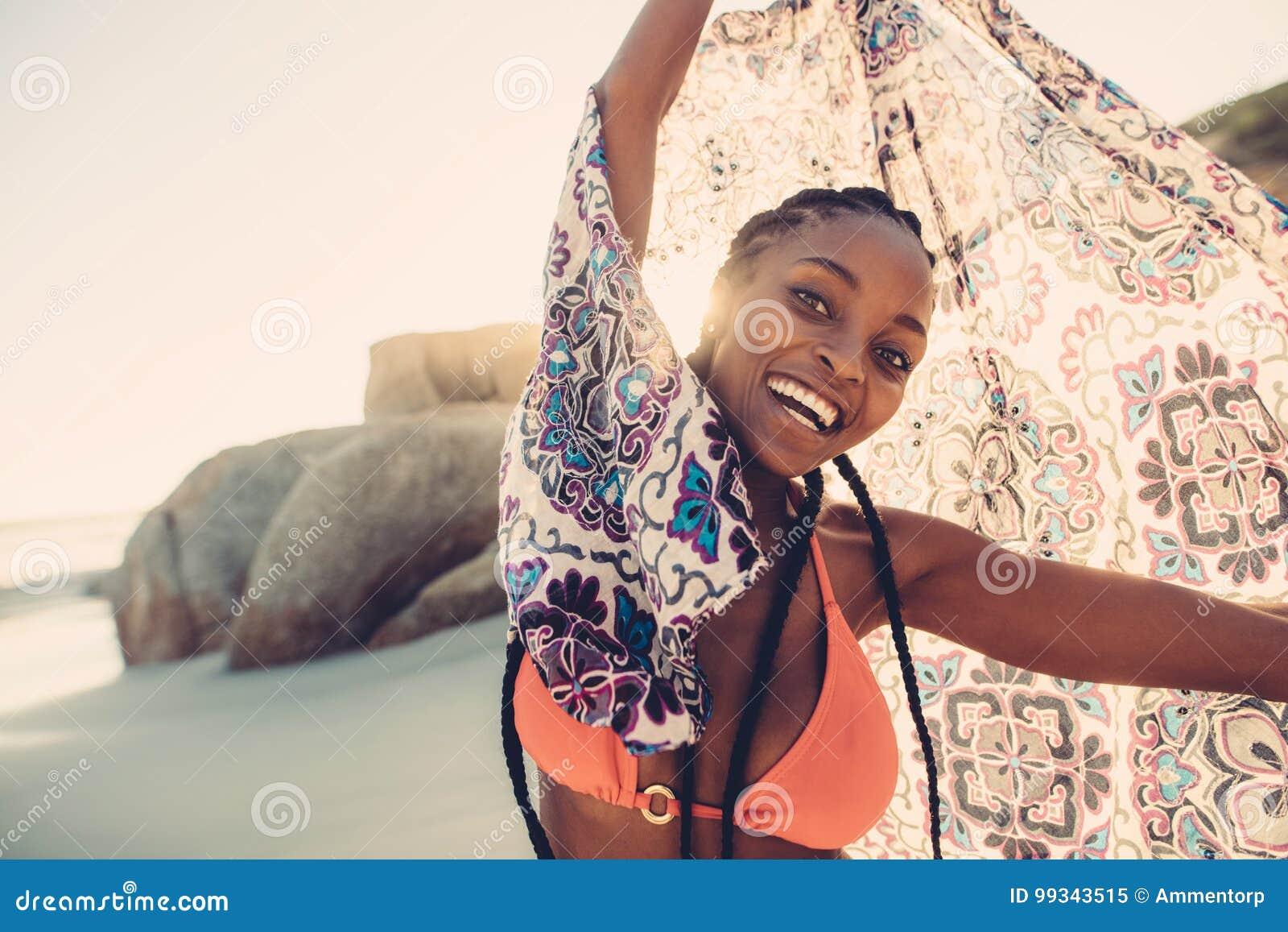0a453c20cbcd Femme africaine jouant avec son écharpe sur la plage Beau tissu se tenant  femelle au-dessus de sa tête et sourire à l appareil-photo
