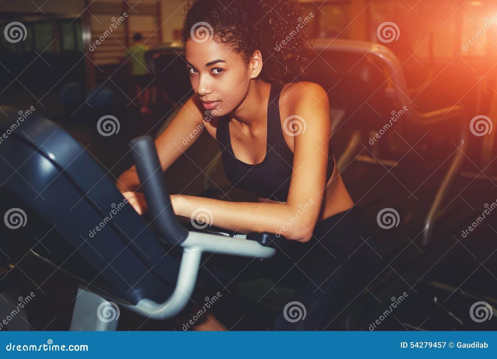 Femme afro-américaine établissant sur le vélo de rotation au gymnase