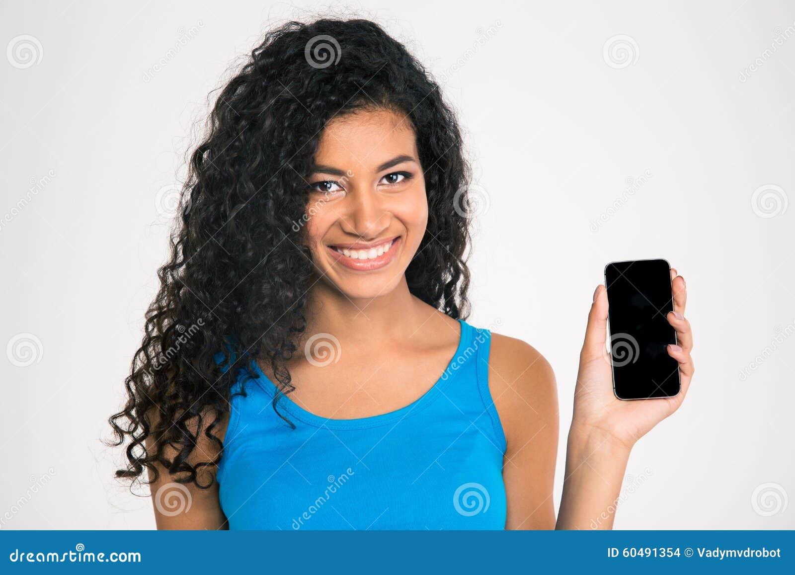Femme afro-américaine de sourire montrant l écran vide de smartphone