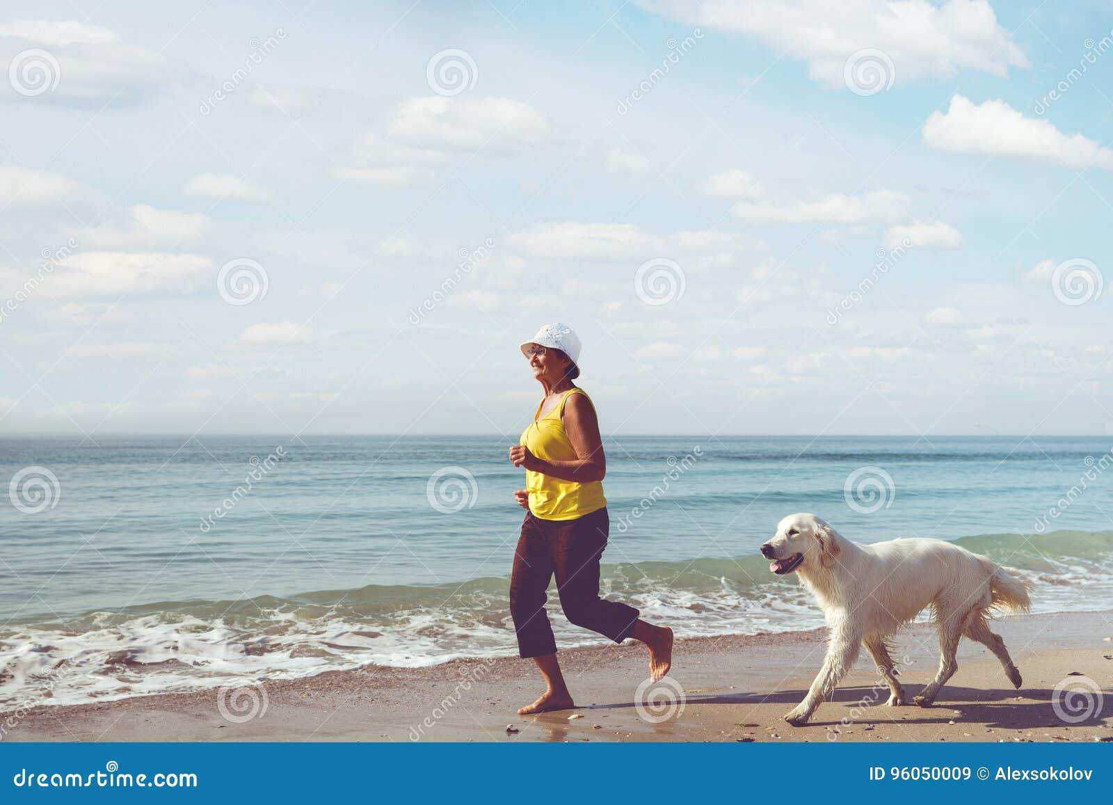 Femme agée courant avec son chien d arrêt de golder