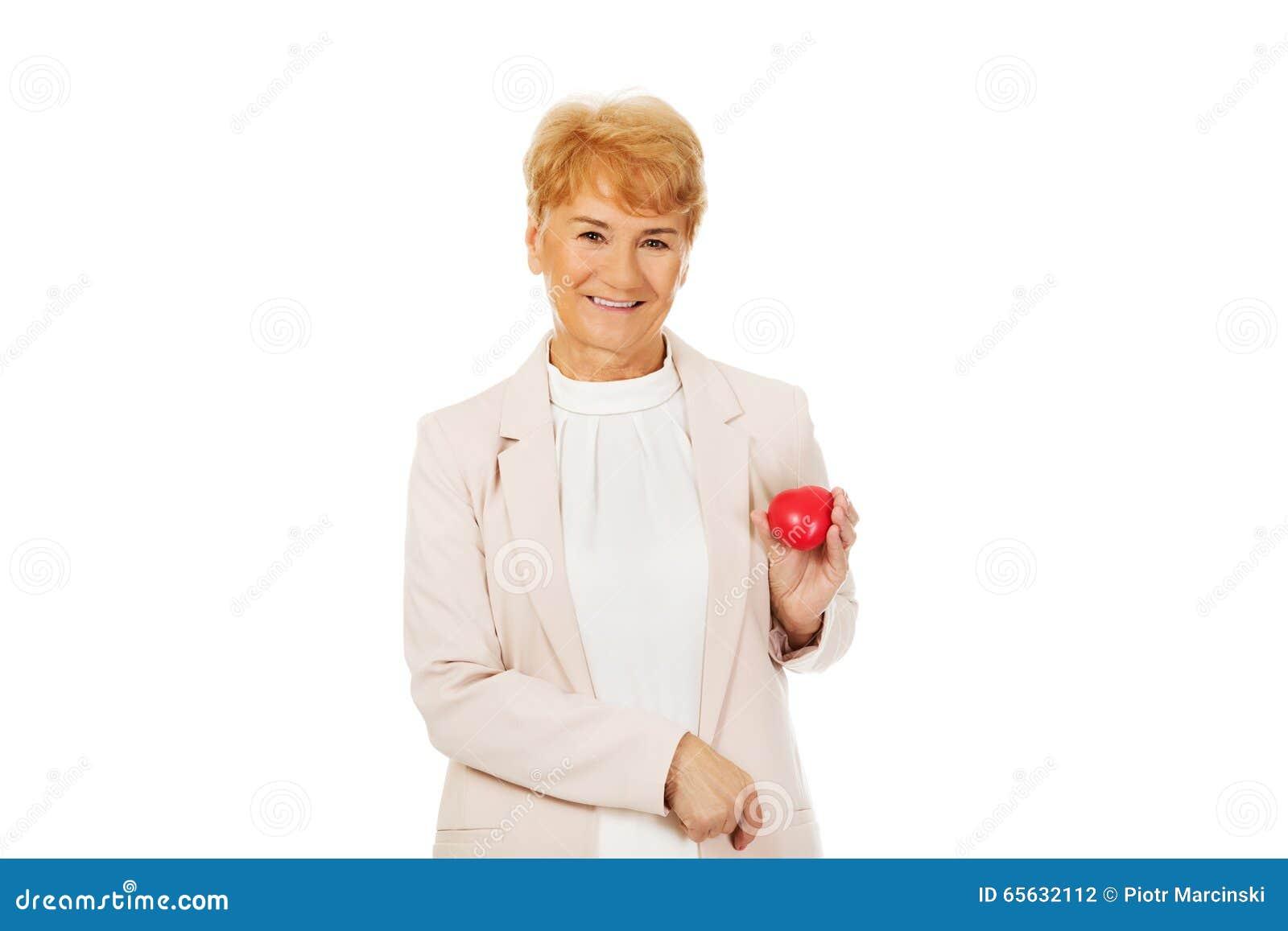 Femme agée de sourire tenant le modèle de coeur