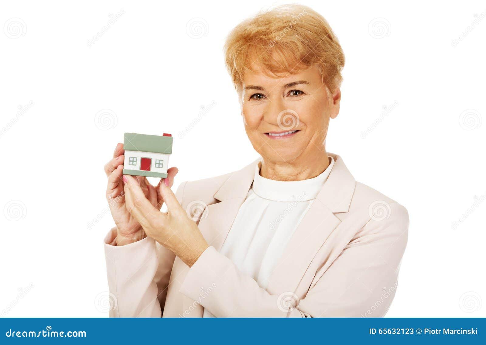 Femme agée de sourire tenant le modèle de maison