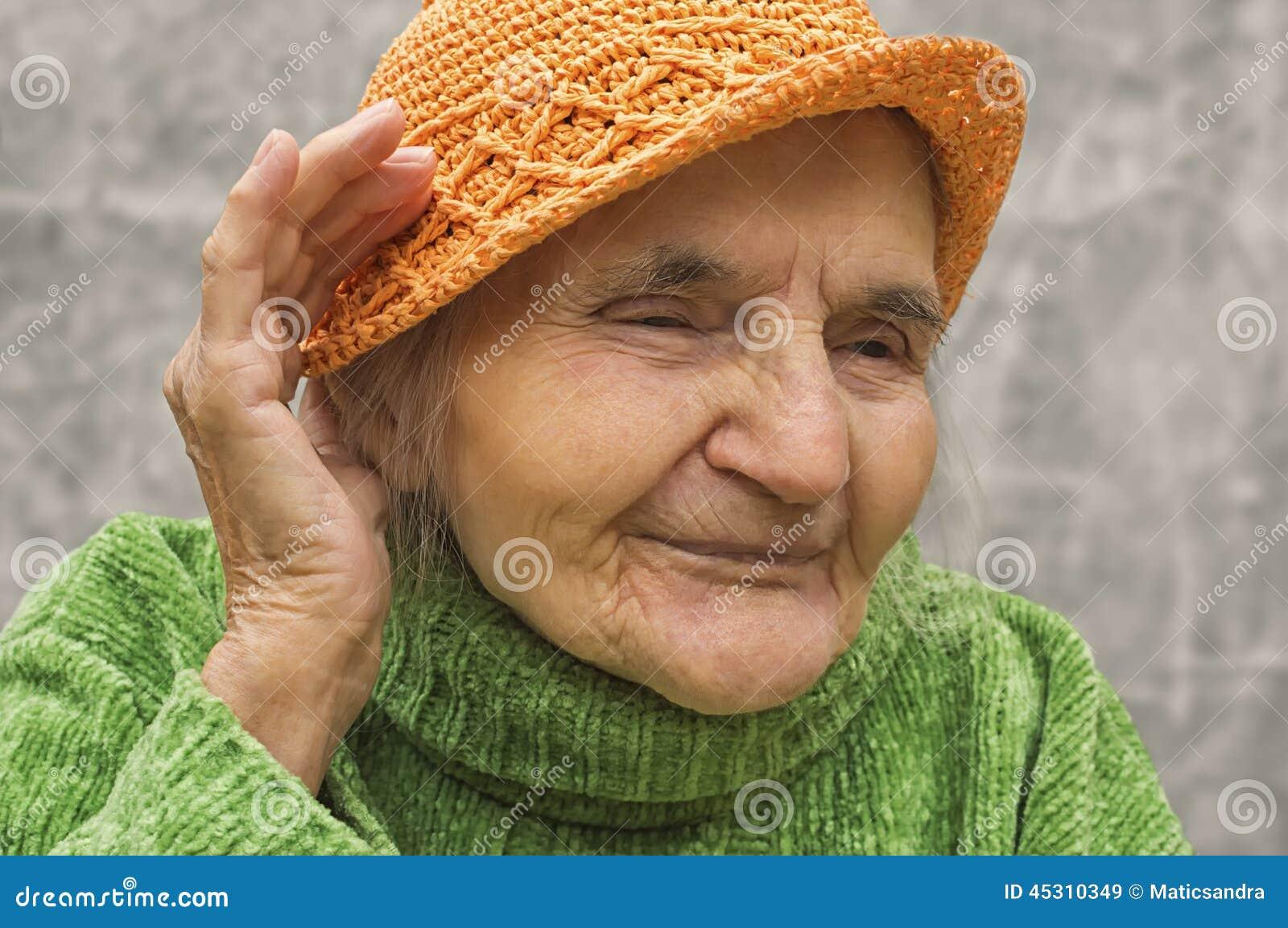 Femme agée tenant la main près d une oreille
