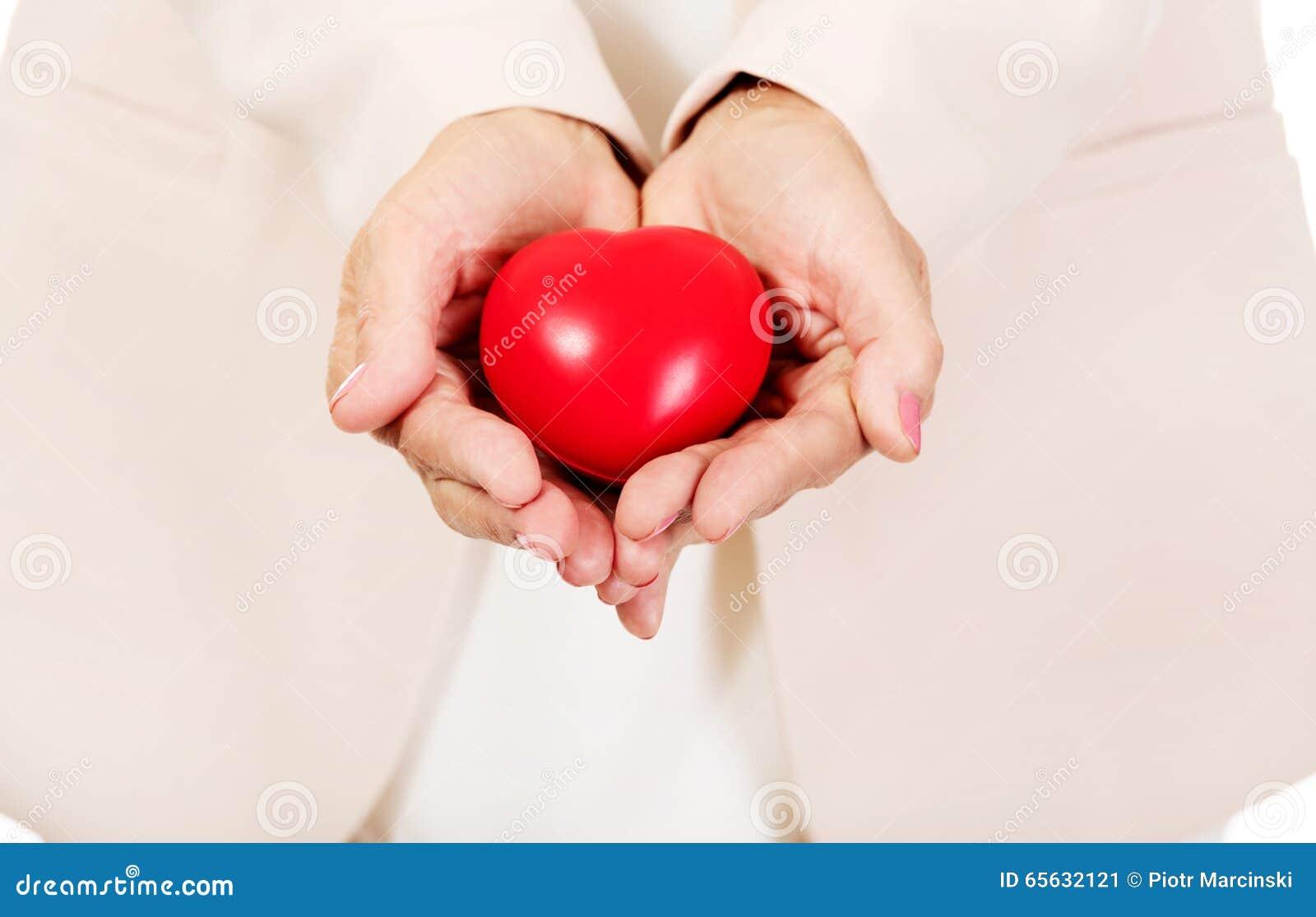 Femme agée tenant le modèle de coeur sur les paumes ouvertes