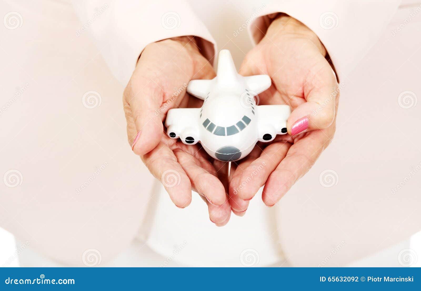 Femme agée tenant un avion de jouet sur les plams ouverts