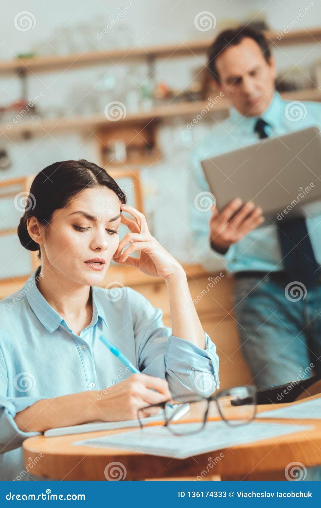 Femme agréable écrivant ses idées sur le papier