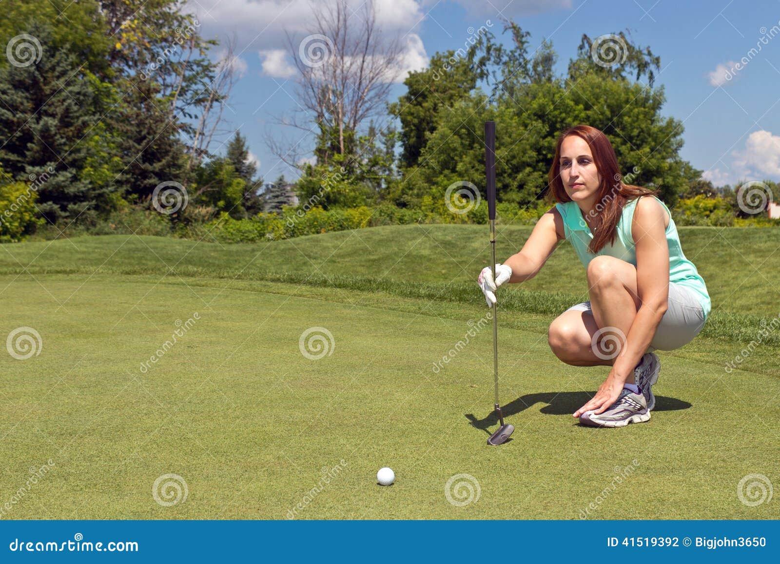 Femme alignant son putt sur le vert de golf