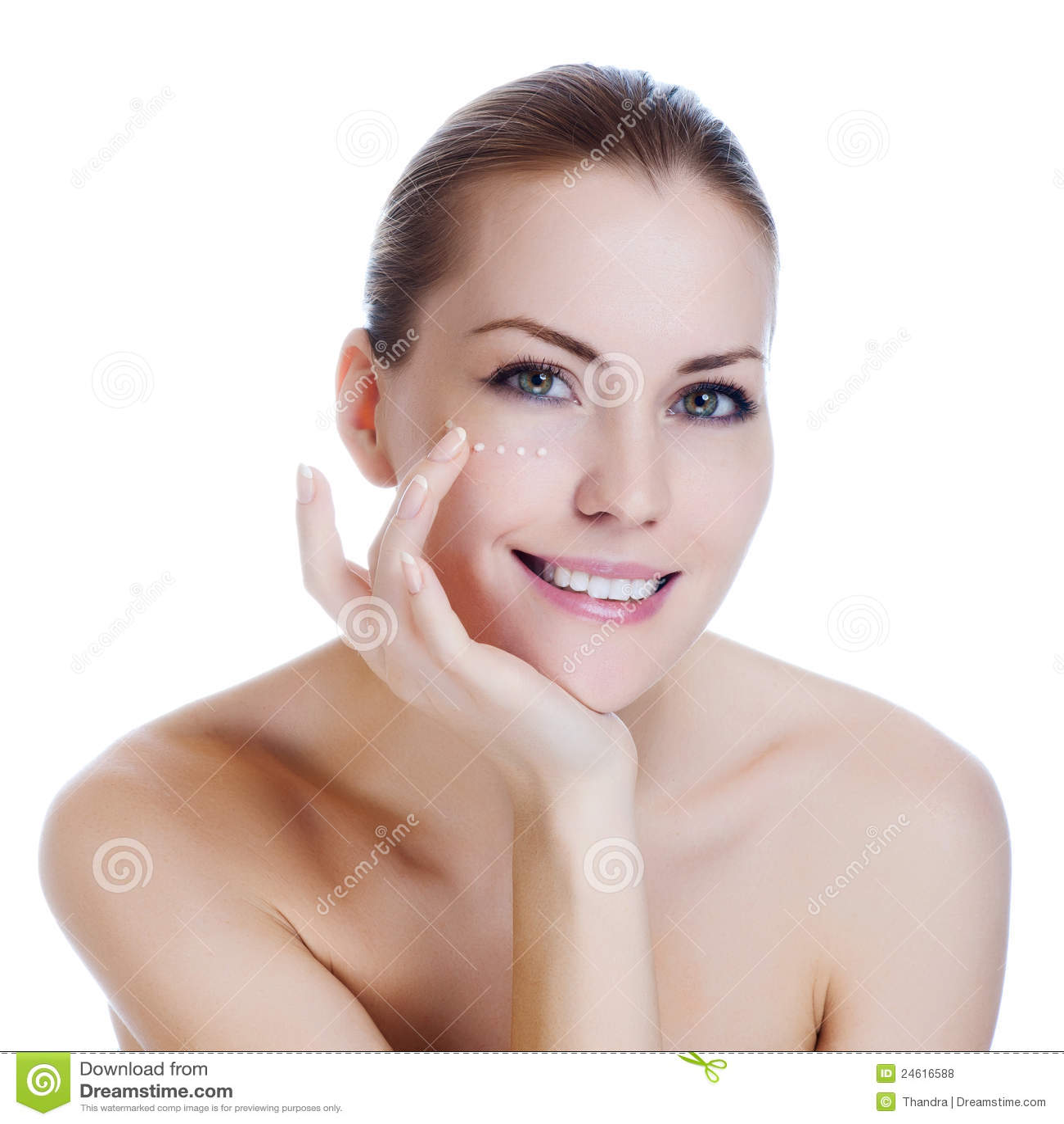 Femme appliquant la crème cosmétique sur la peau près des yeux