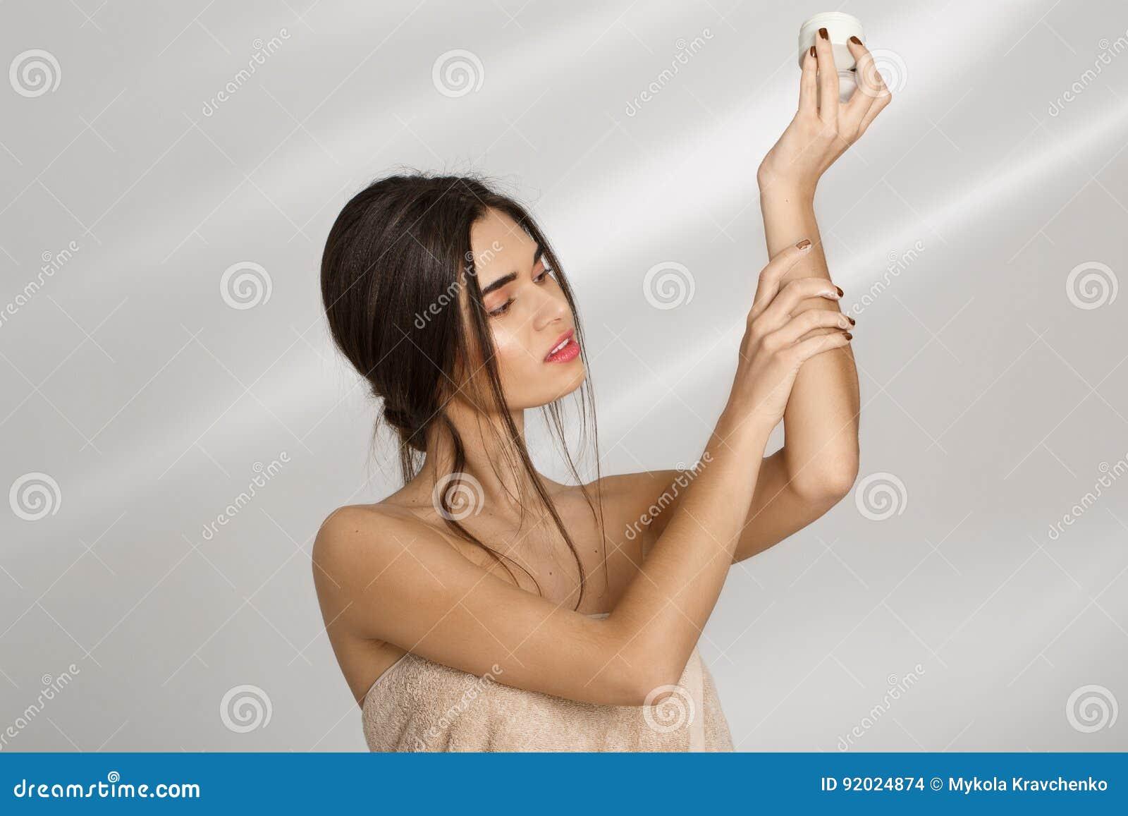 Femme appliquant la crème hydratante sur la main gauche après s être baigné Soin de beauté