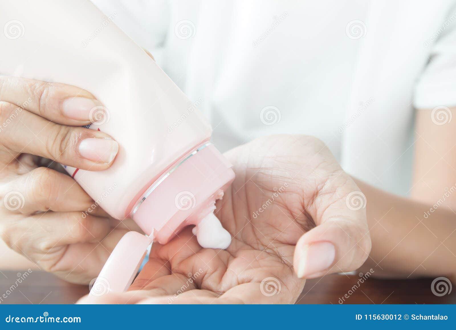 Femme appliquant la lotion sur sa main, concept de beauté