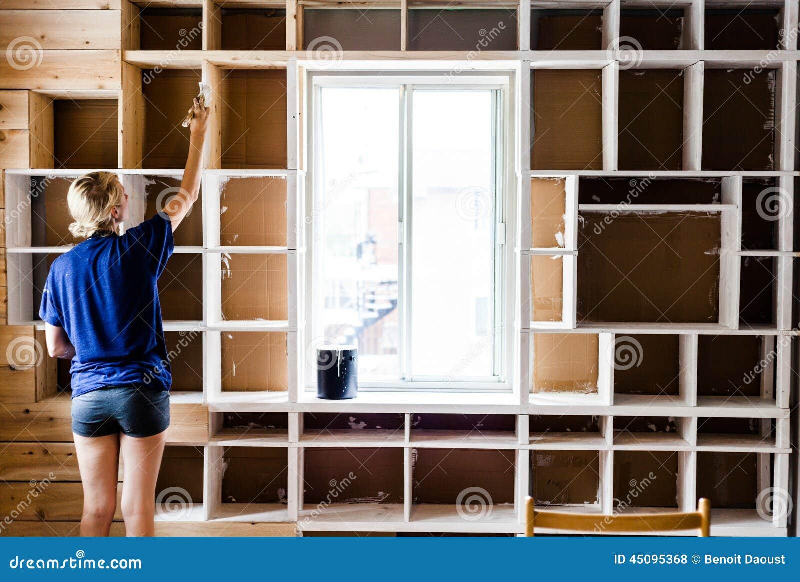 femme appliquant la premi re couche de peinture sur une biblioth que en bois photo stock image. Black Bedroom Furniture Sets. Home Design Ideas