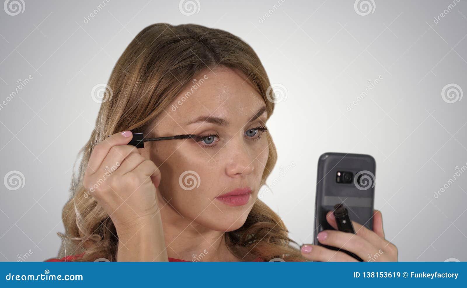 Femme appliquant le mascara noir sur des cils regardant dans son téléphone sur le fond de gradient