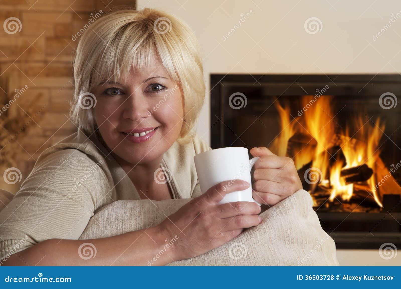 Femme appréciant la boisson chaude par la cheminée à la maison