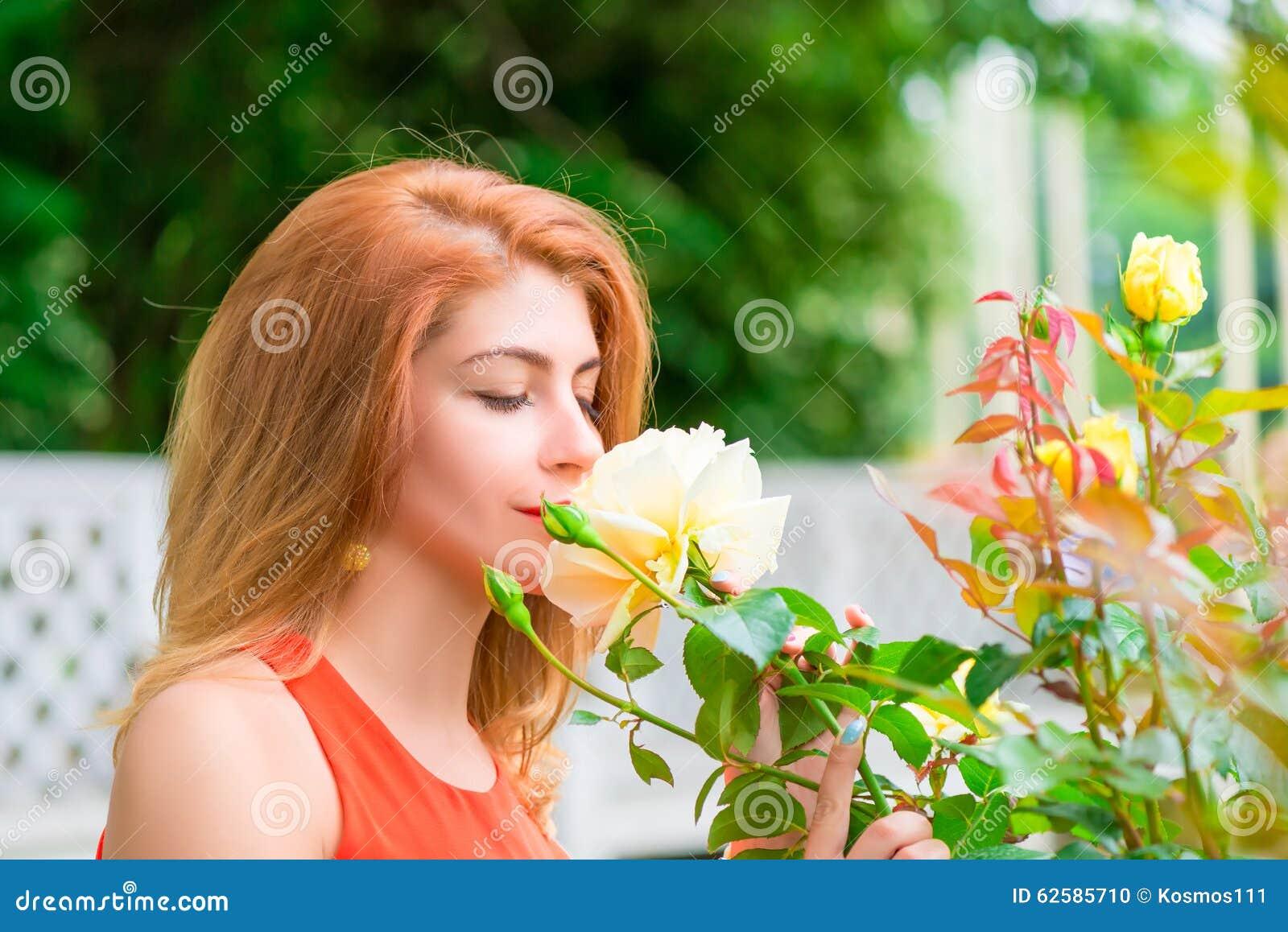 Femme appréciant le parfum des roses de floraison