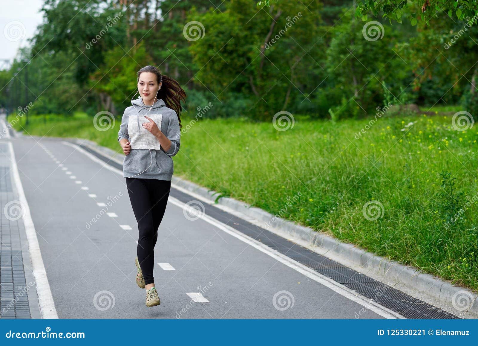 Femme asiatique courante sur le bord de mer Pulser de matin Les trains d athlète