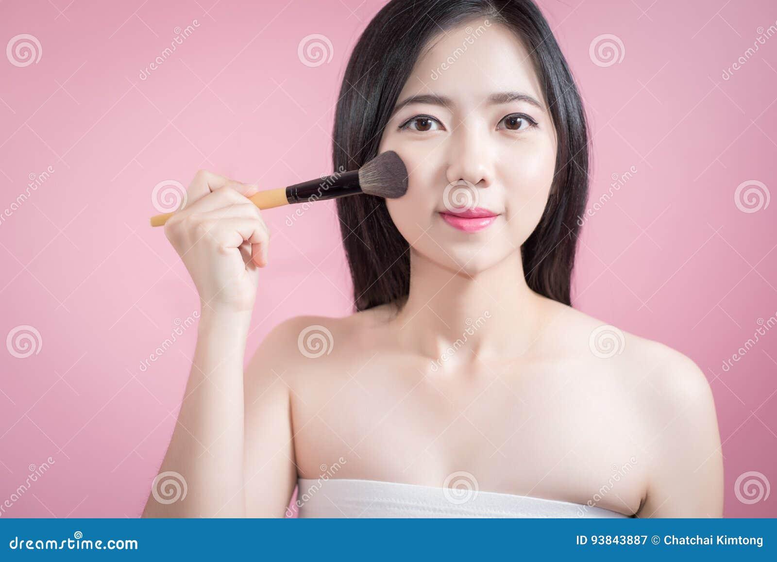 Femme asiatique de longs cheveux jeune belle appliquant la brosse cosmétique de poudre sur le visage lisse au-dessus du fond rose