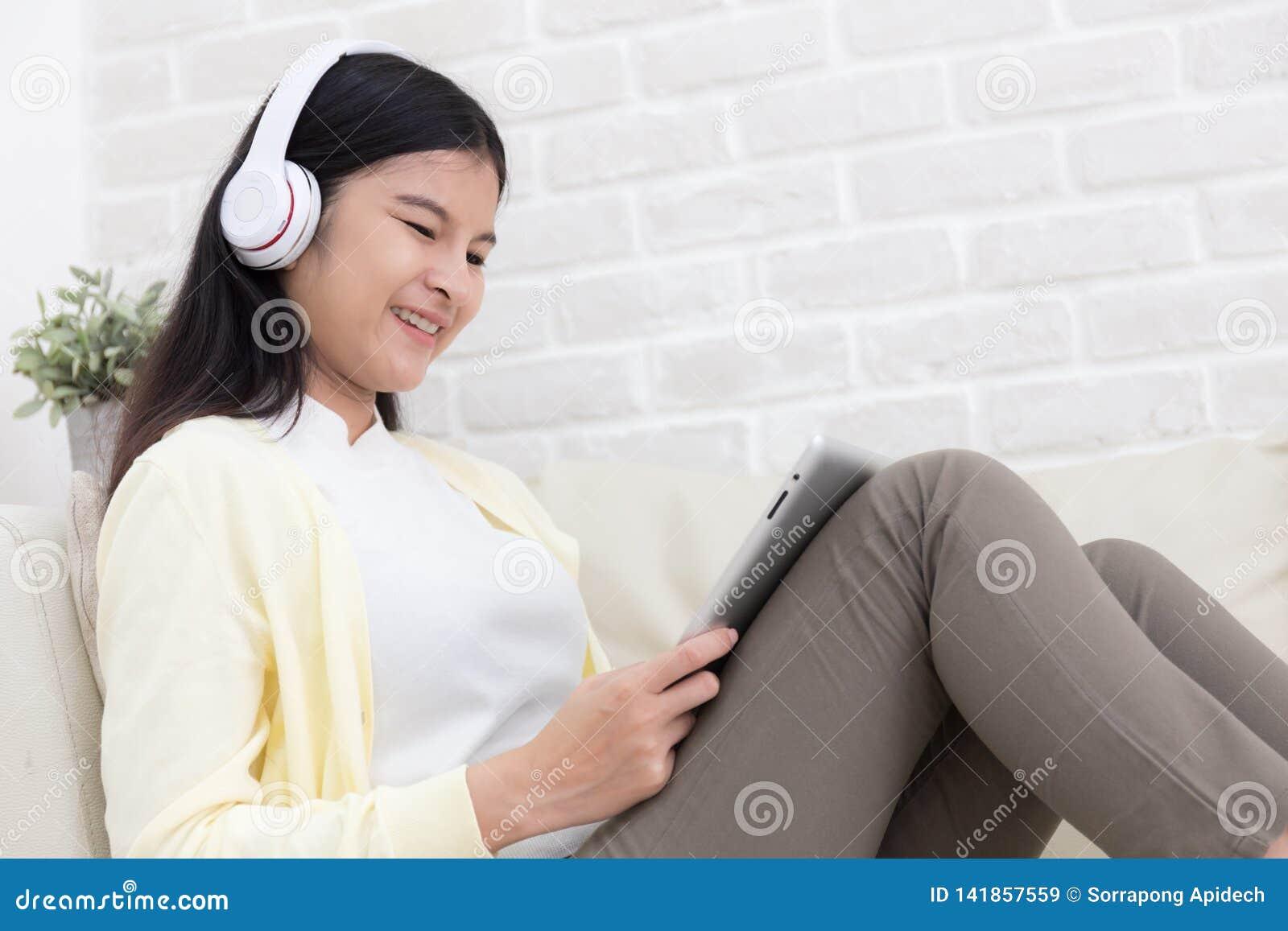 Femme asiatique de sourire à l aide de la tablette et écoutant la musique sur le sofa à la maison dans le salon