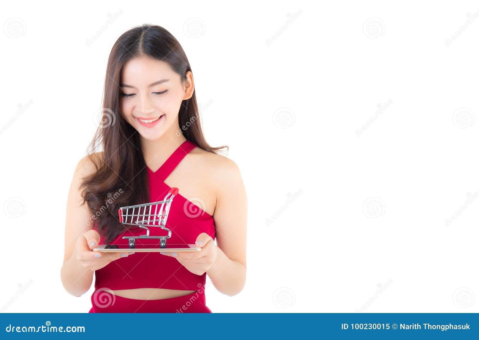 Femme asiatique de sourire dans la robe rouge tenant le comprimé avec l heureux fille et chariot sur le comprimé
