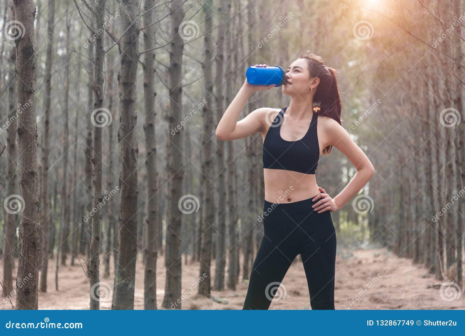 Femme asiatique de sport de beauté reposant et tenant la bouteille d eau potable et détendant au milieu de la forêt après fatigué