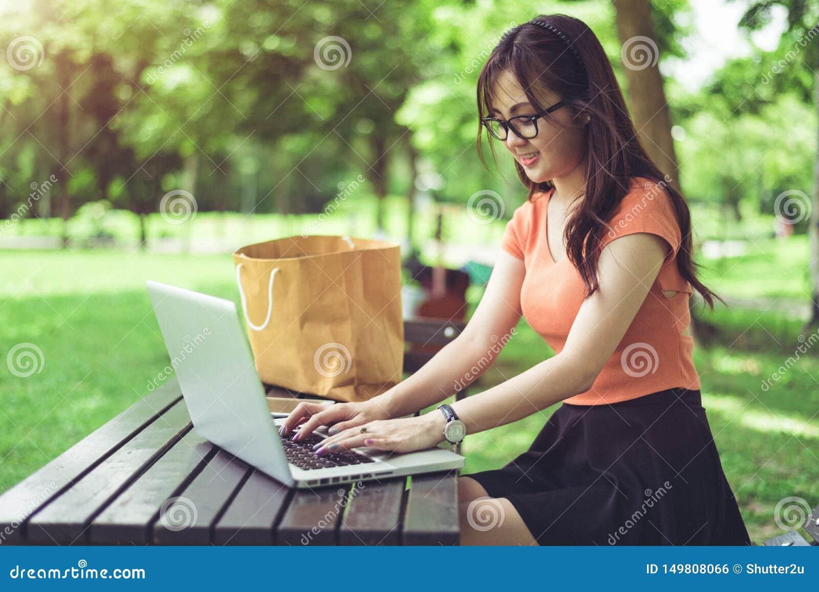 Femme asiatique employant et introduisant au clavier sur le clavier d ordinateur portable le parc d ext?rieur Femme causant ? ses