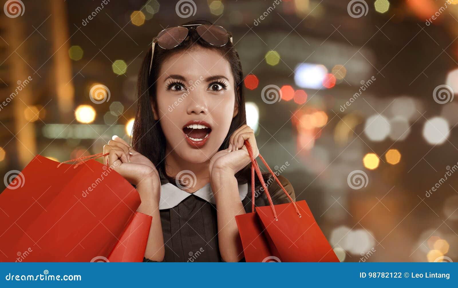 Femme asiatique heureuse avec le panier rouge célébrant Black Friday