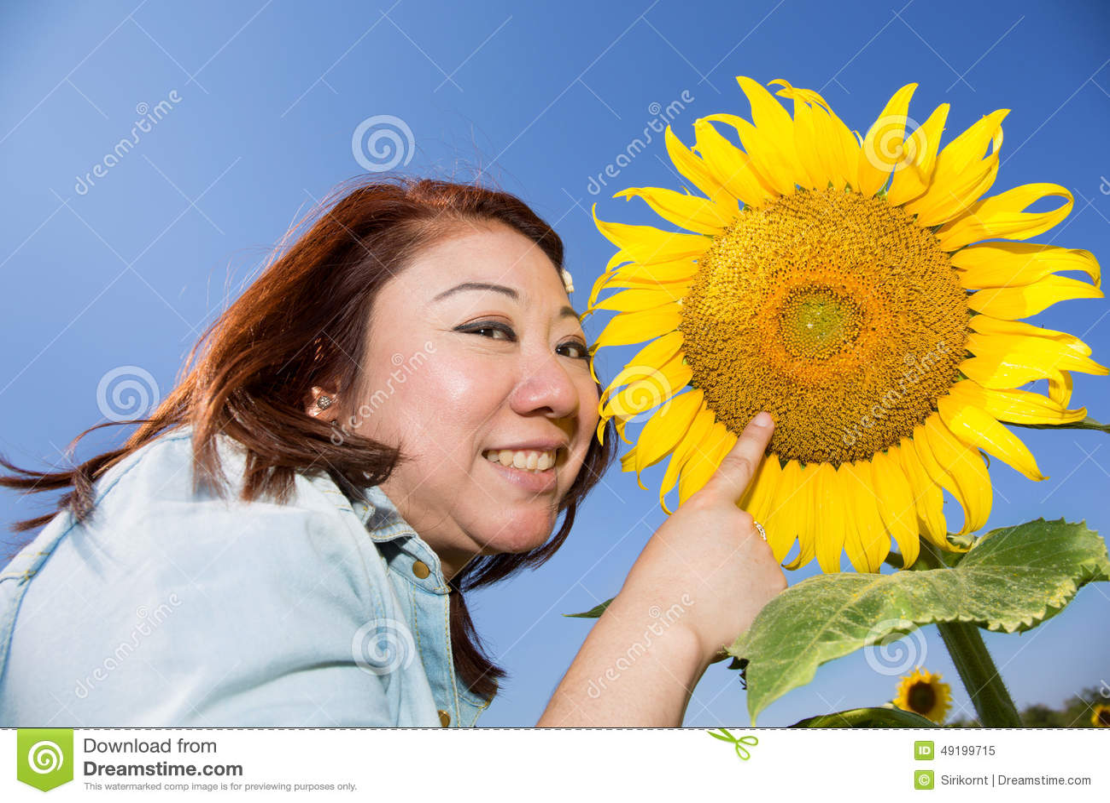 Femme asiatique heureuse dans le domaine de fleur de tournesol
