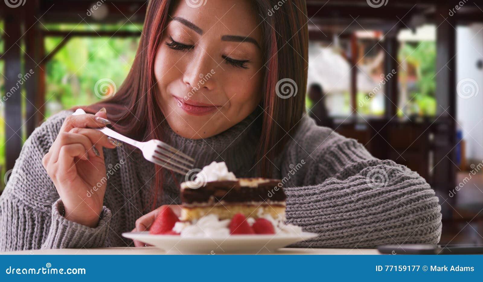 Femme asiatique heureuse mangeant le gâteau à la maison