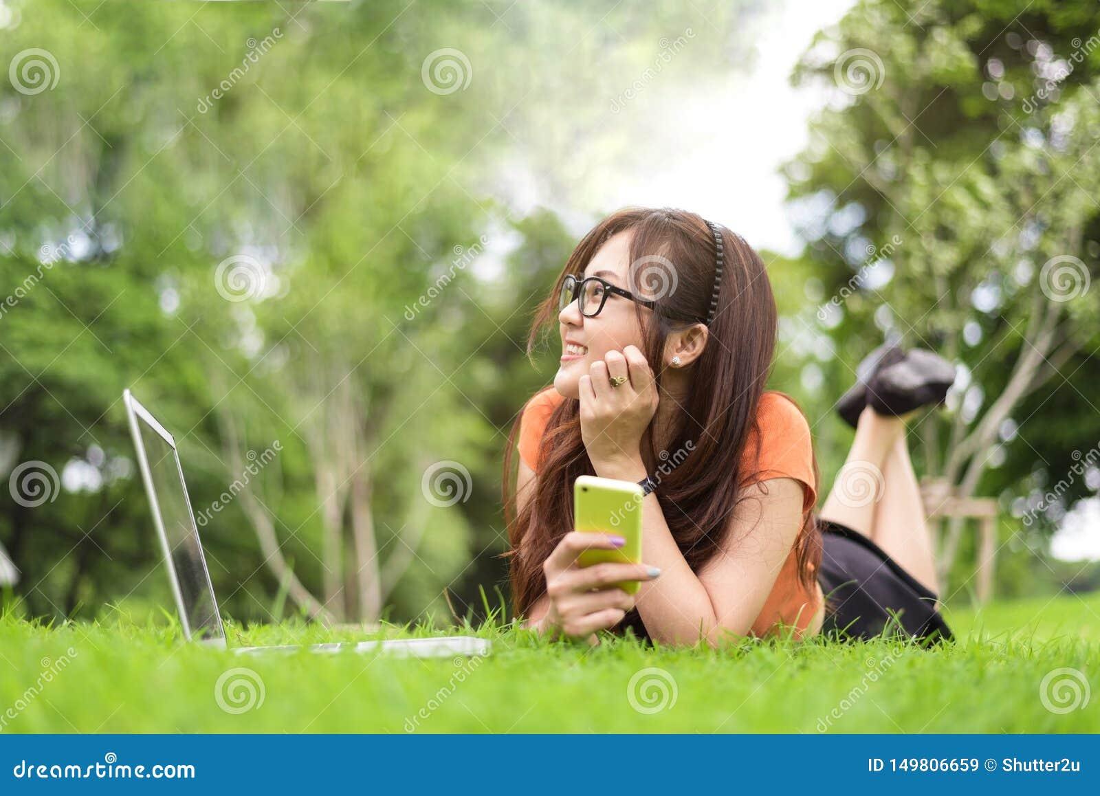 Femme asiatique heureuse se reposant et regardant ? cot? en parc avec le smartphone Les gens et le concept de modes de vie Th?me