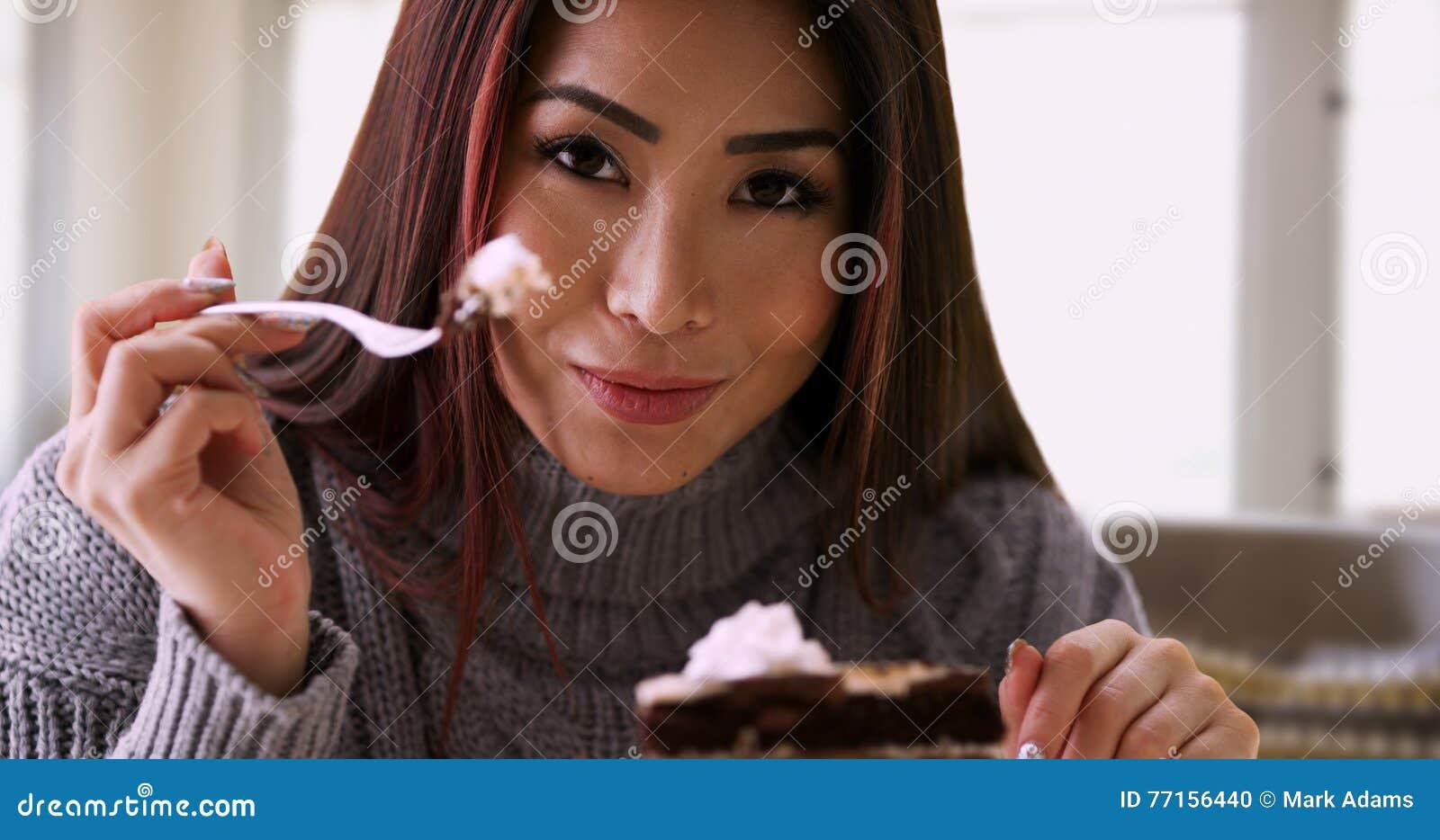 Femme asiatique heureuse souriant avec le gâteau à la maison
