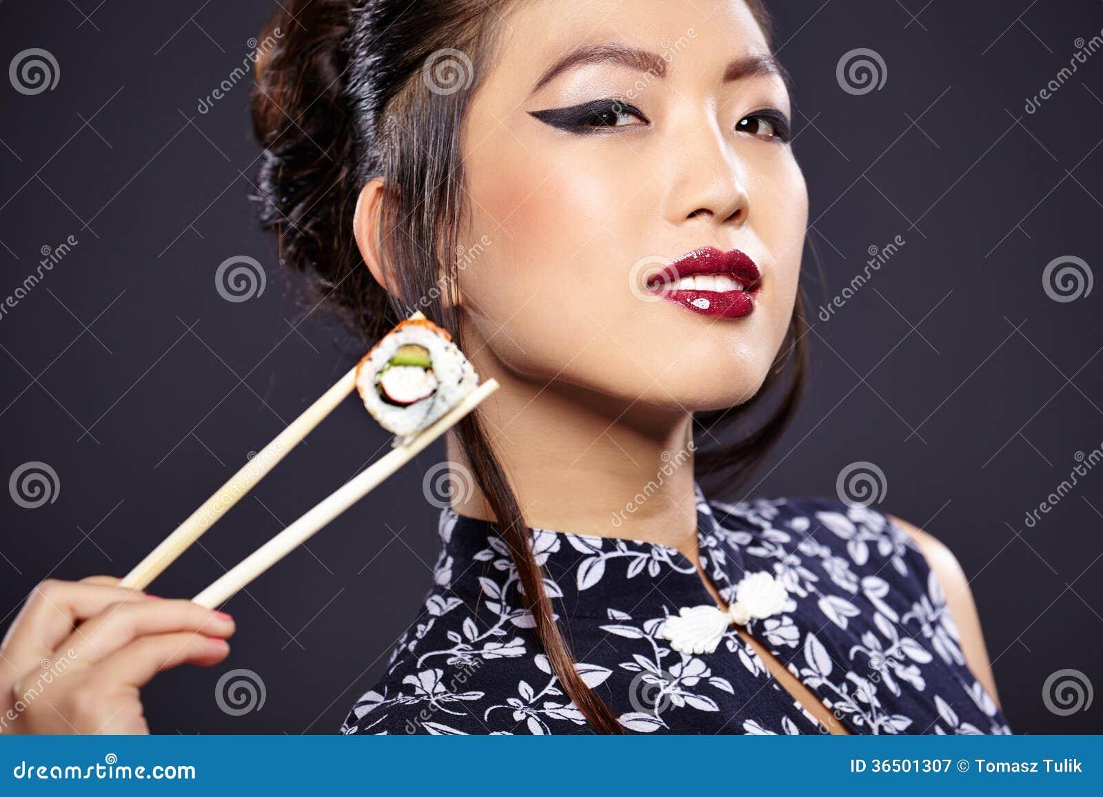 Femme asiatique mangeant des sushi,