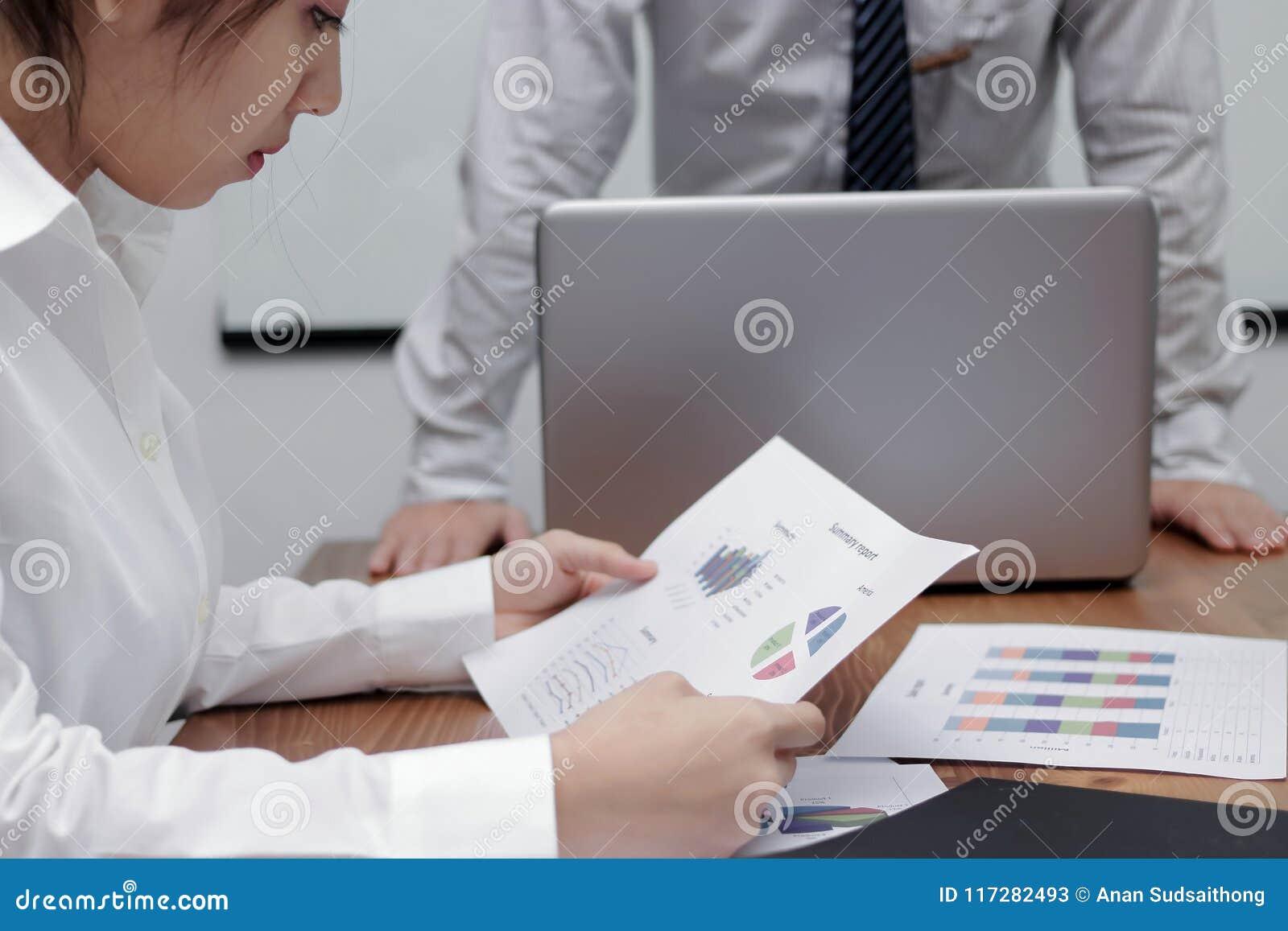 Femme asiatique soumise à une contrainte d affaires analysant des diagrammes ou des écritures au cours de la réunion dans la sall