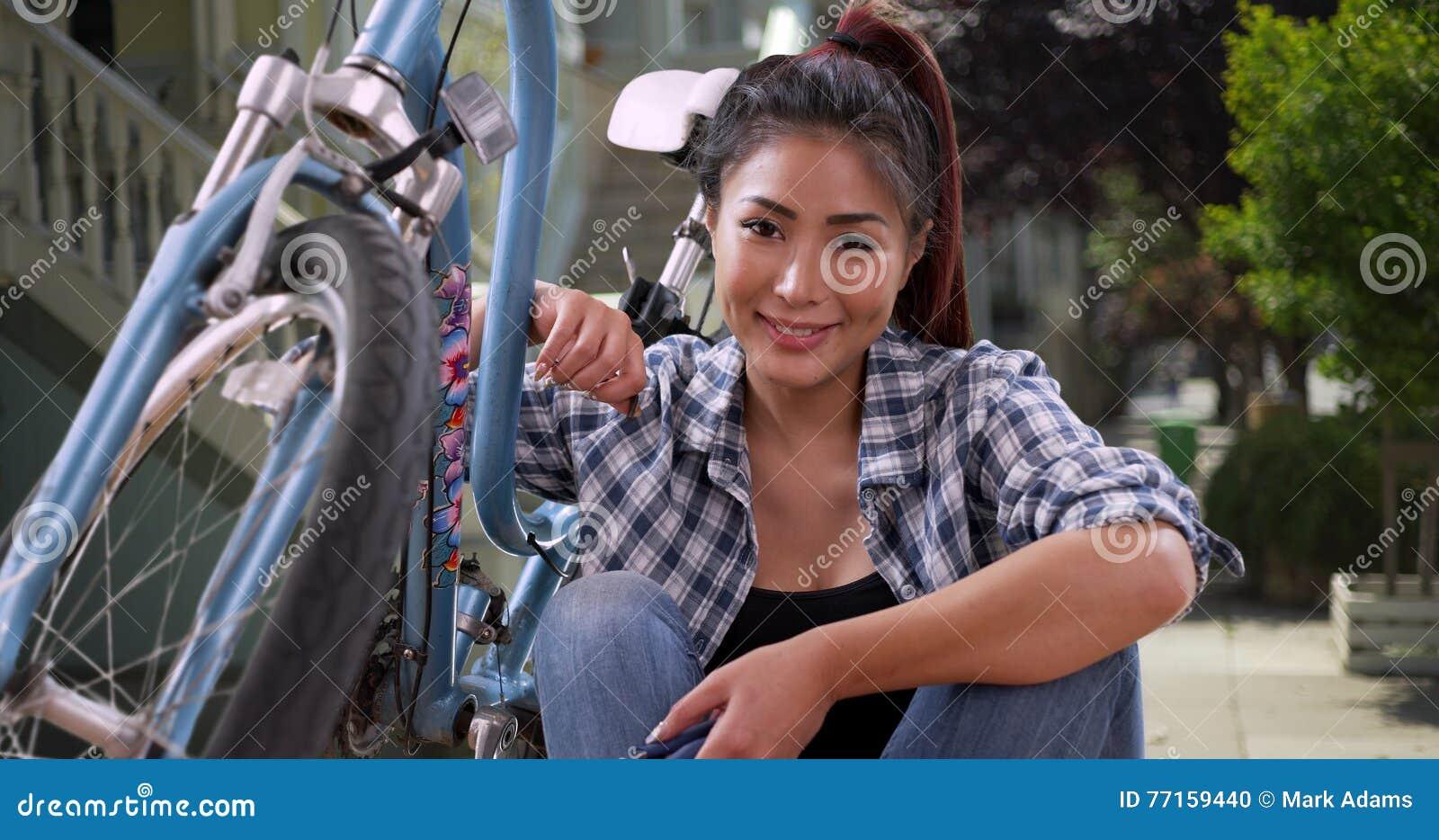 Femme asiatique souriant avec son vélo