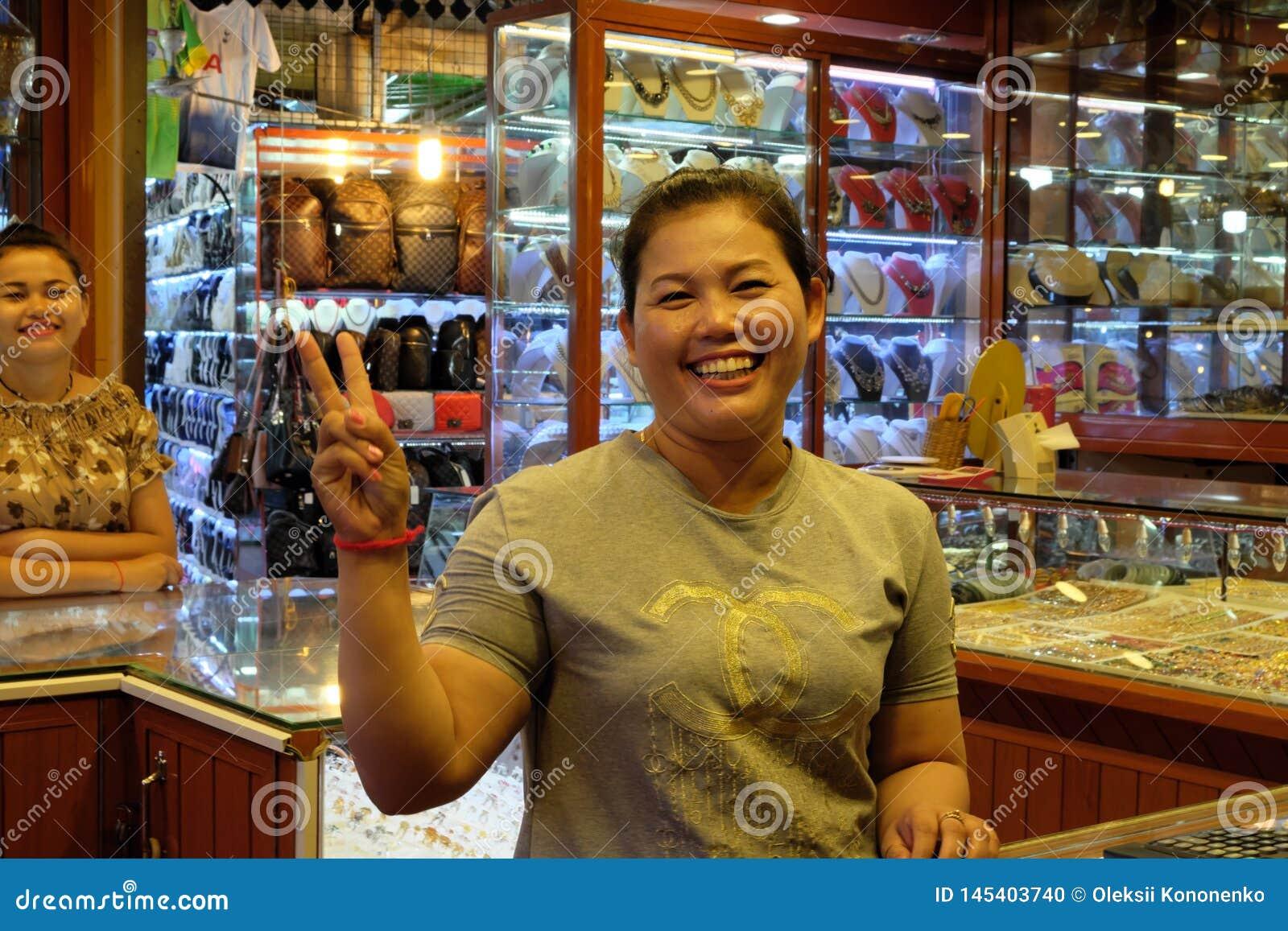 Femme asiatique souriant et faisant des gestes, vendeur de bijoux