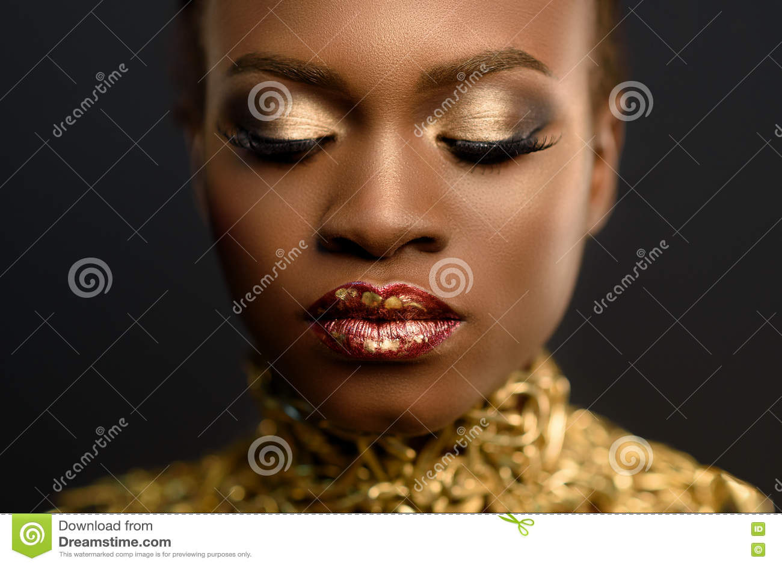 Femme assez africaine de jeunes, avec des cheveux recueillis dans la coiffure et le maquillage sensible d or, posant sur le fond