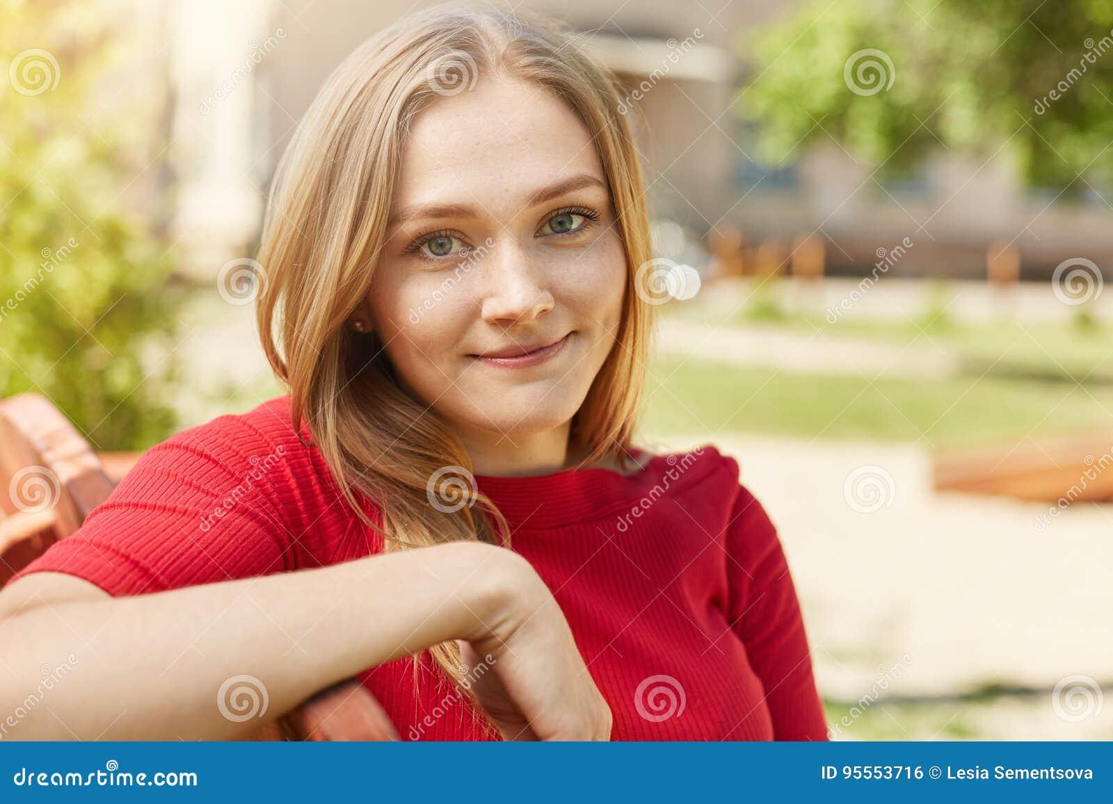 Femme assez aux yeux bleus avec les cheveux justes détendant dehors tout en se reposant au banc regardant directement dans la réj