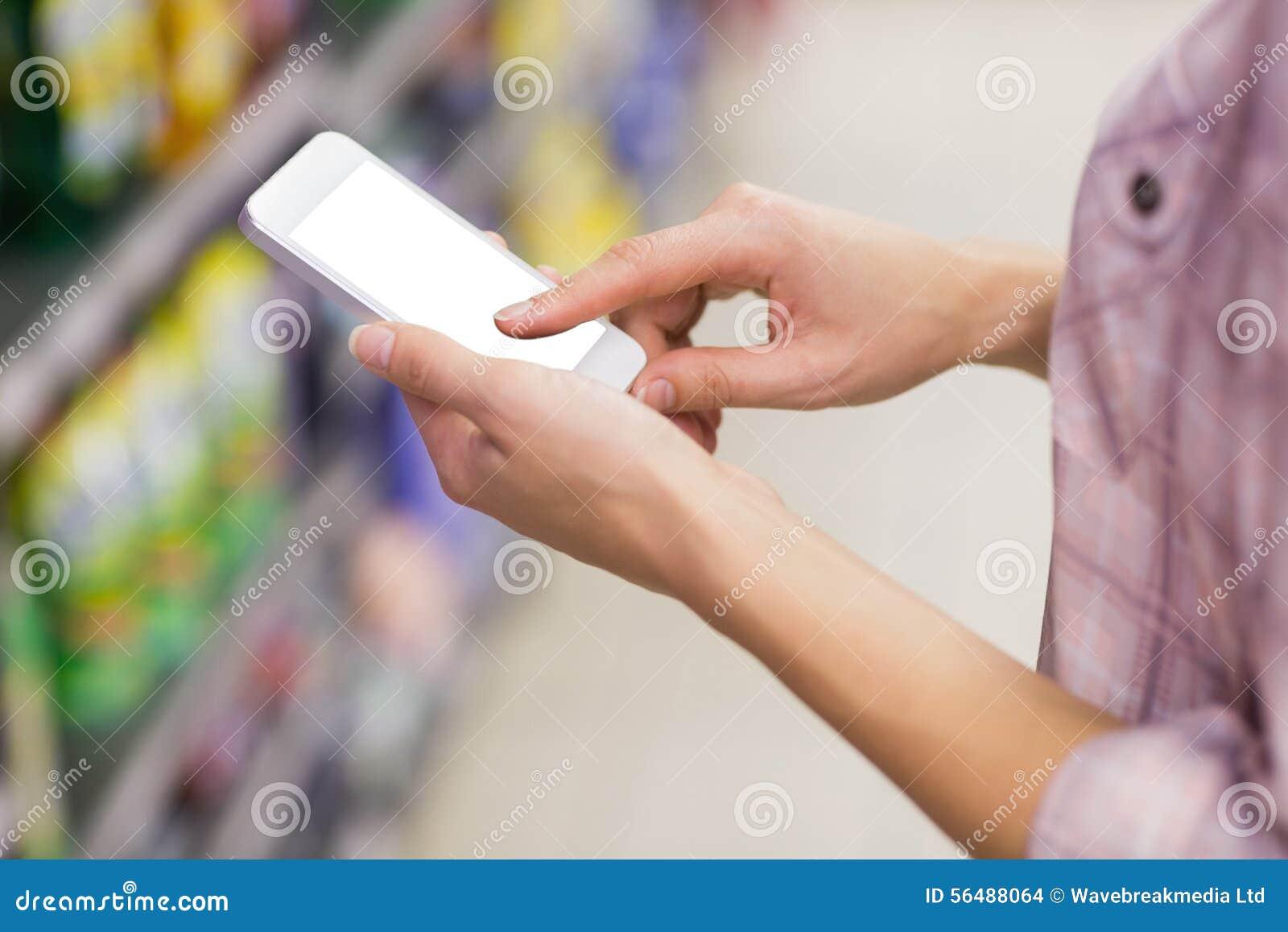 Femme assez blonde à l aide de son smartphone