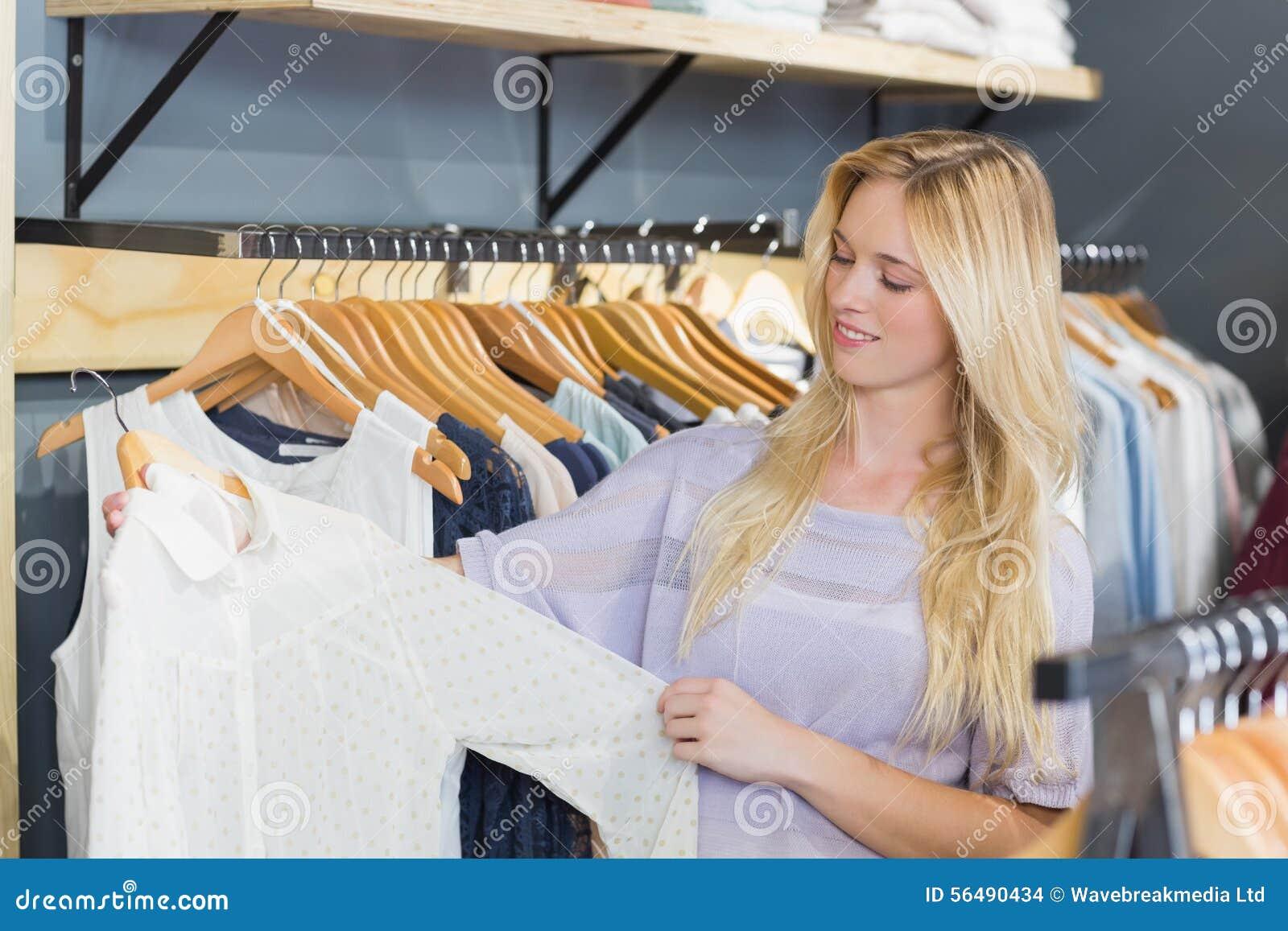 Femme assez blonde choisissant des vêtements