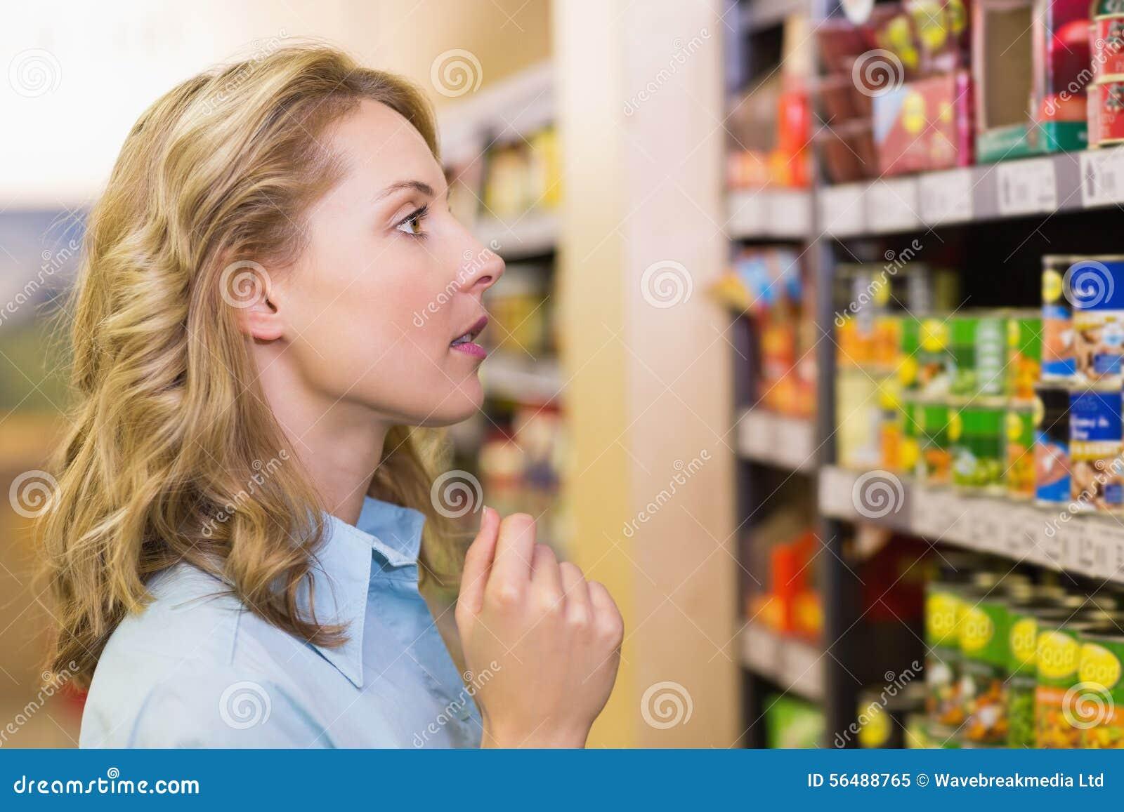 Femme assez blonde regardant des étagères
