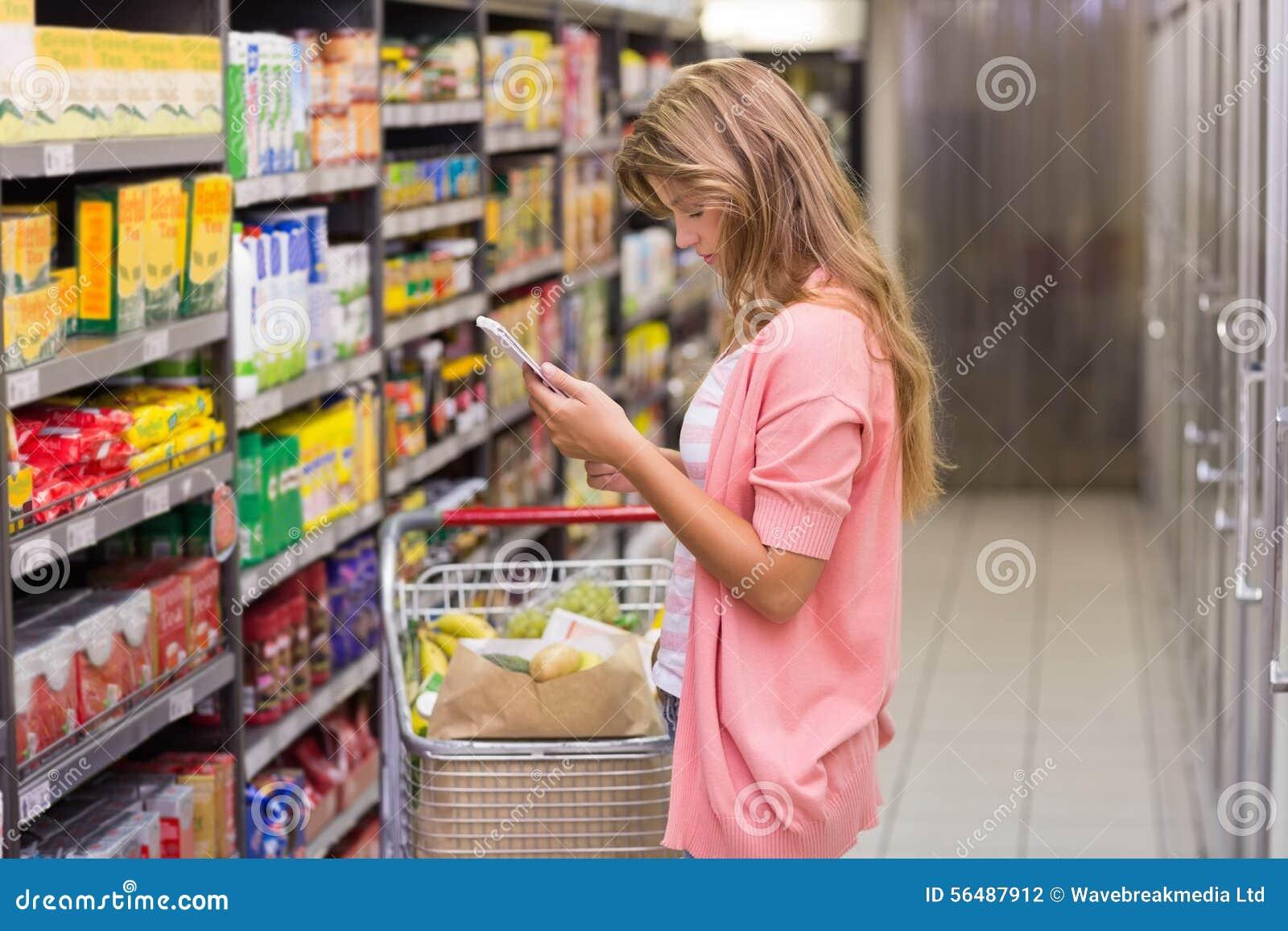 Femme assez blonde regardant un produit