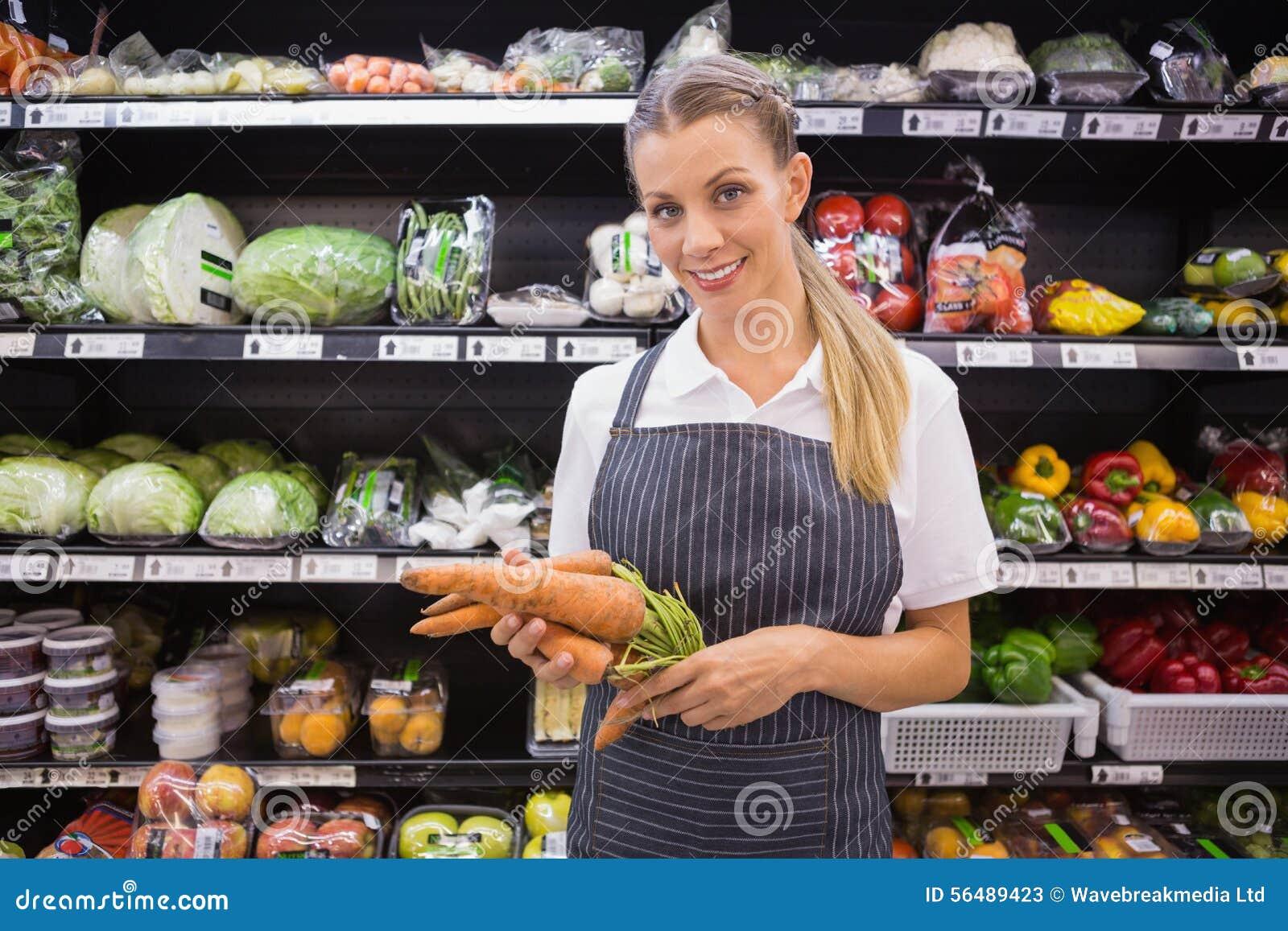 Femme assez blonde tenant la carotte et regardant l appareil-photo