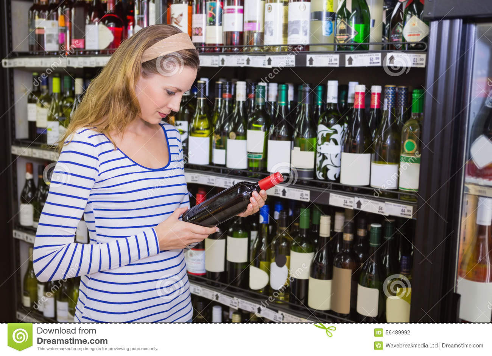 Femme assez blonde tenant une bouteille de vin rouge