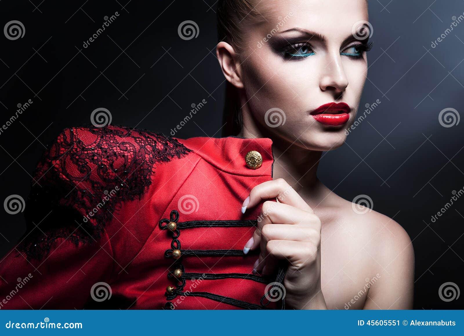 Femme attirante érotique en rouge avec des yeux bleus