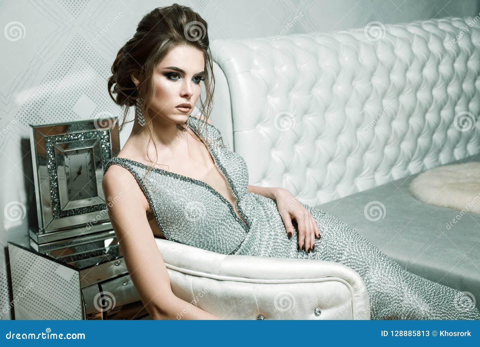 Femme attirante avec la coiffure élégante et le maquillage lumineux dans l evenin
