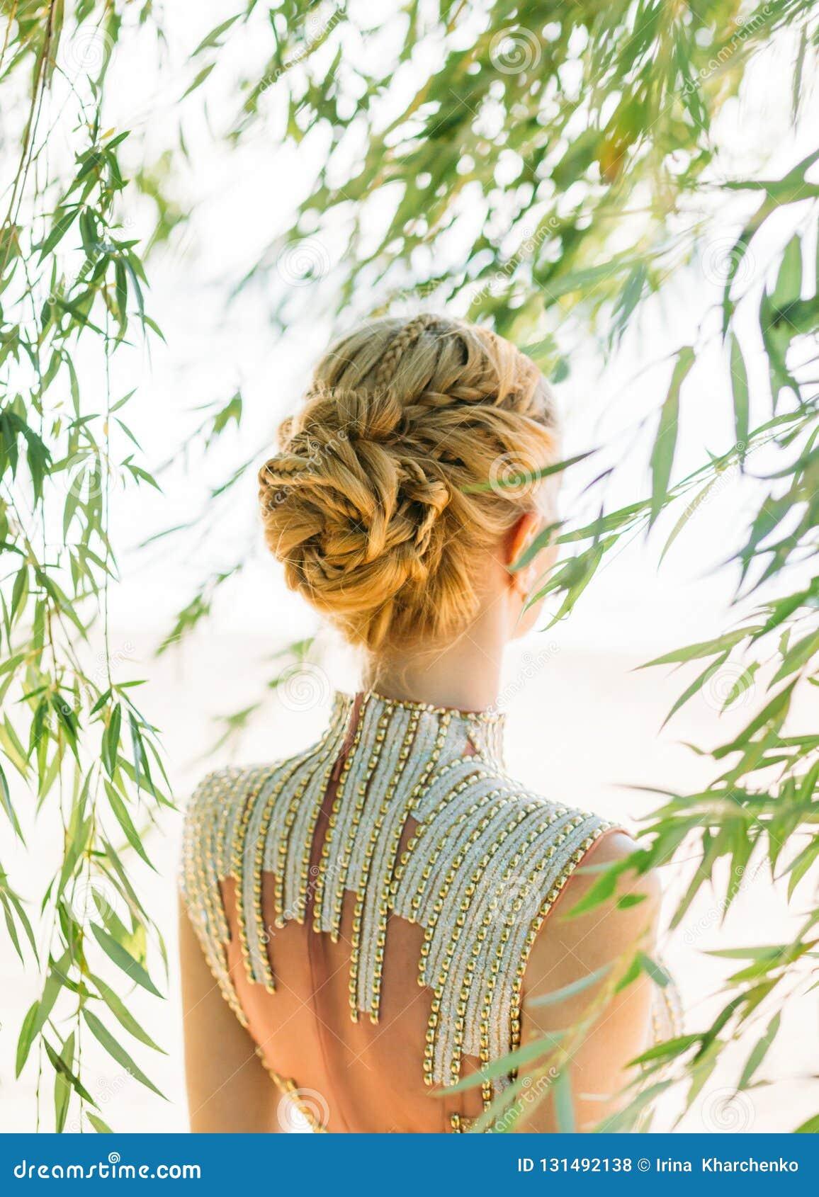 Femme attirante avec les cheveux blonds blonds droits, tressés dans une coiffure douce des tresses pour une princesse ou un elfe,