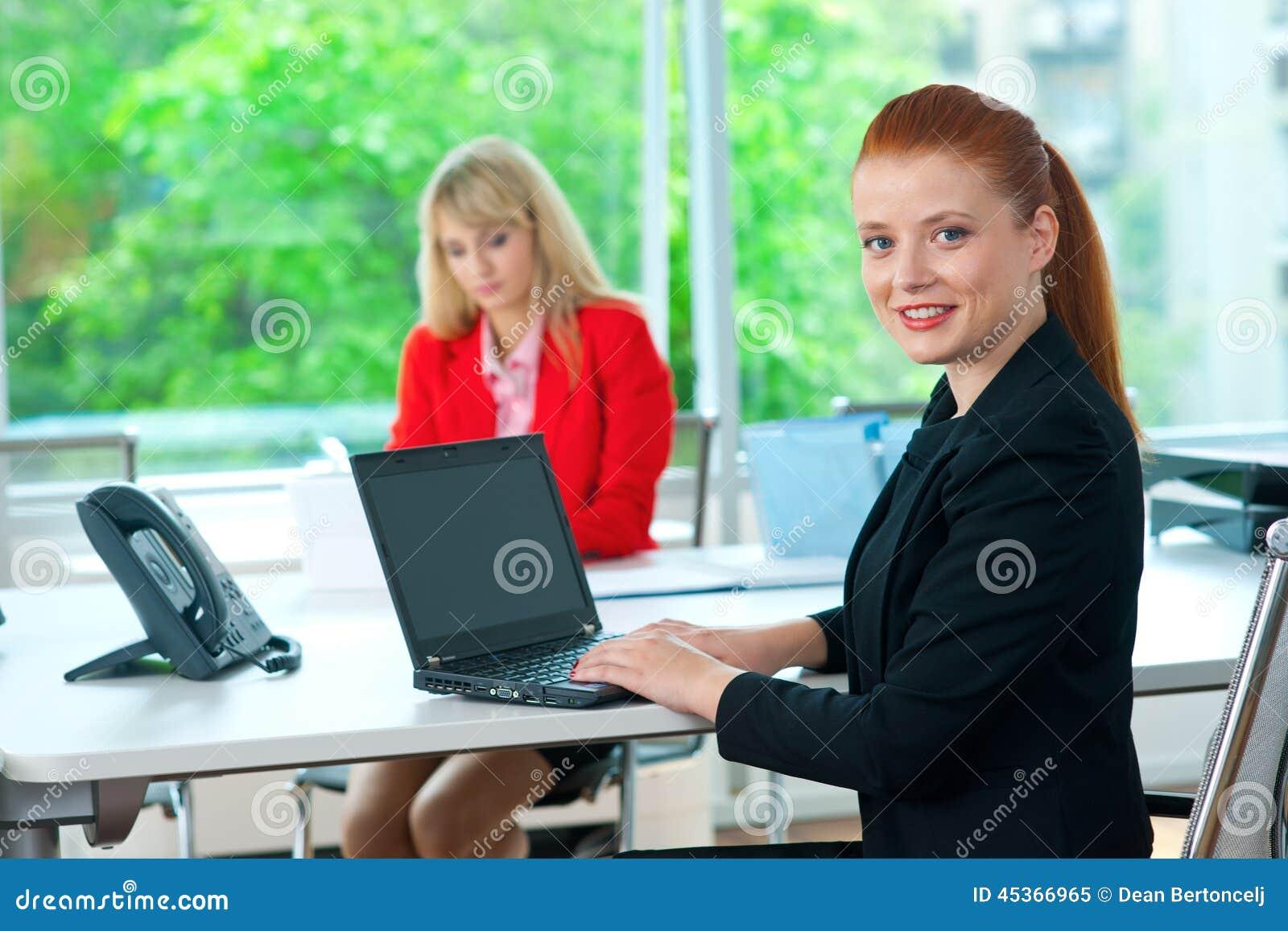 Femme attirante d affaires dans le bureau avec le collègue à l arrière-plan